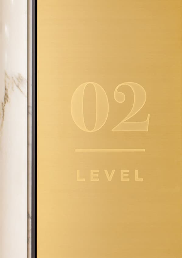 PacMutual Building gold level identity signage on marble wall.