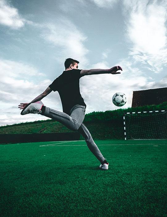 Man swinging his leg back preparing to kick a soccer ball on a grassy field