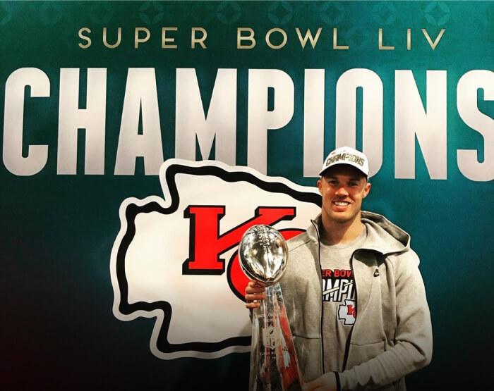 NFL Champion Daniel Sorensen celebrates the Kansas City Chiefs victory holding a trophy.