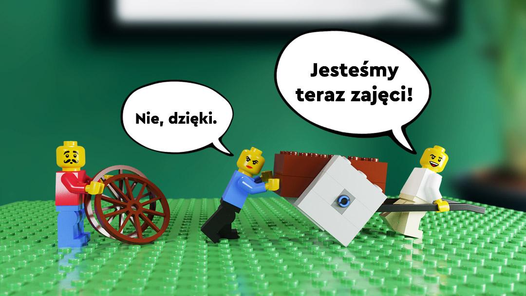 Ludziki LEGO pchające wóz na kwadratowych kolach. Kolega sugerujacy zmianę na okrągłe kola