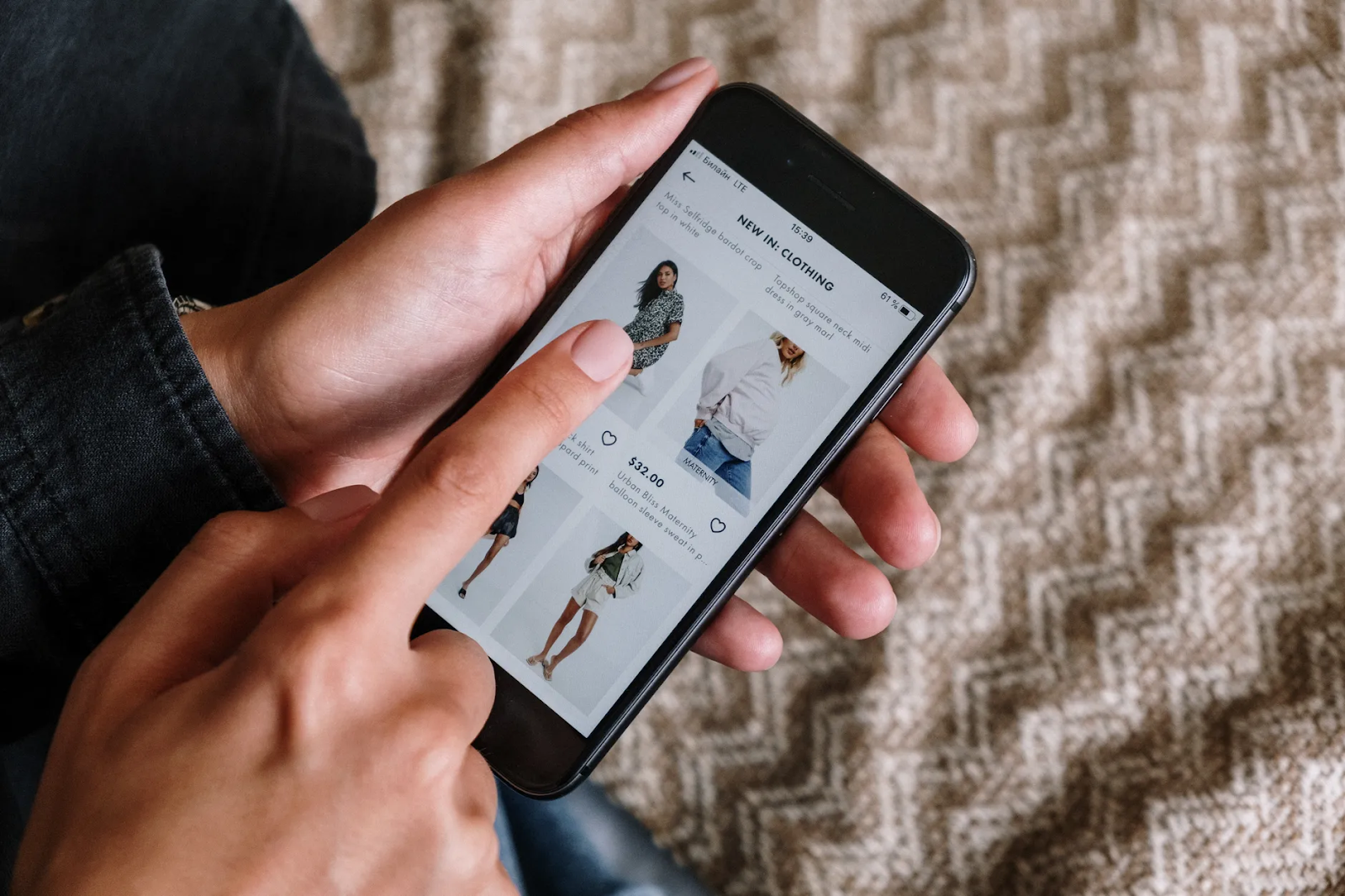 Person scrolling through an eCommerce app for clothes