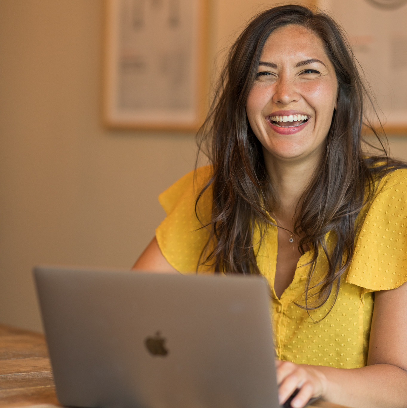 Smiling woman in front of laptop looking into the camera