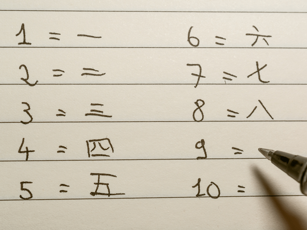 Persona escribiendo números en Chino en un cuaderno