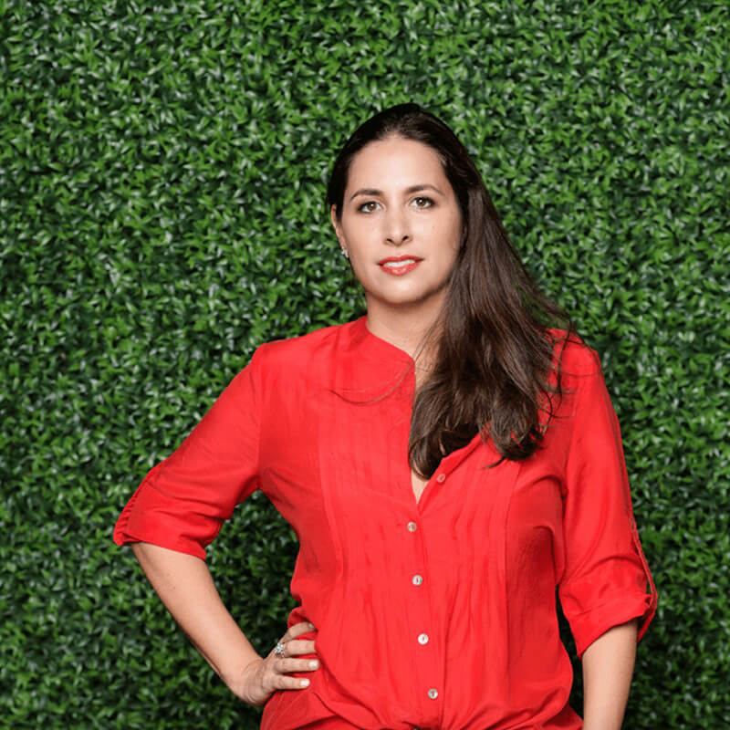 Nicole dressed in a bright red blouse poses in front of covered green leaves wall.she is Plan design creative director ans managing partner