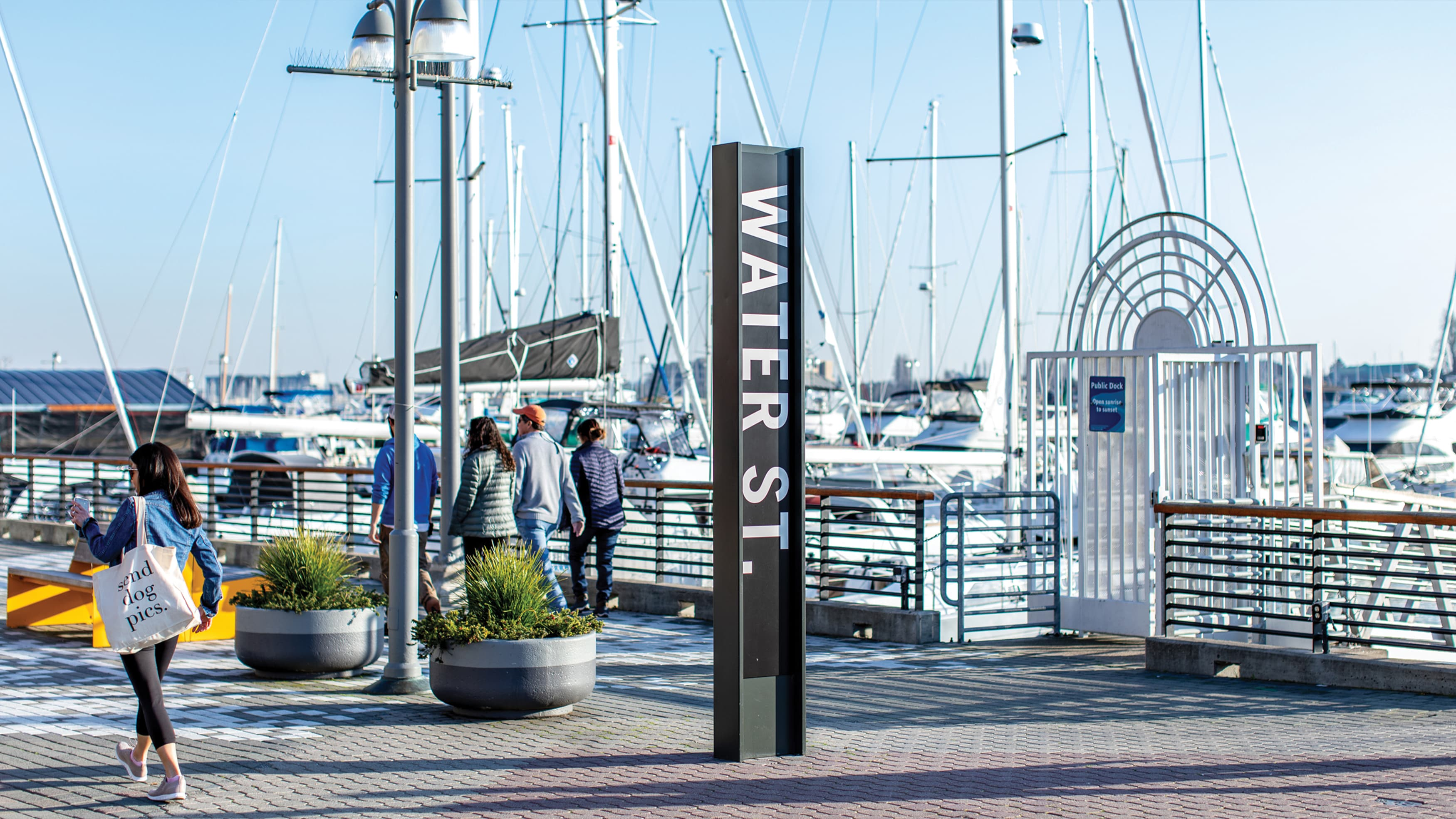 Oakland's historic Water Street at Jack London Square signage and pedestrians walking