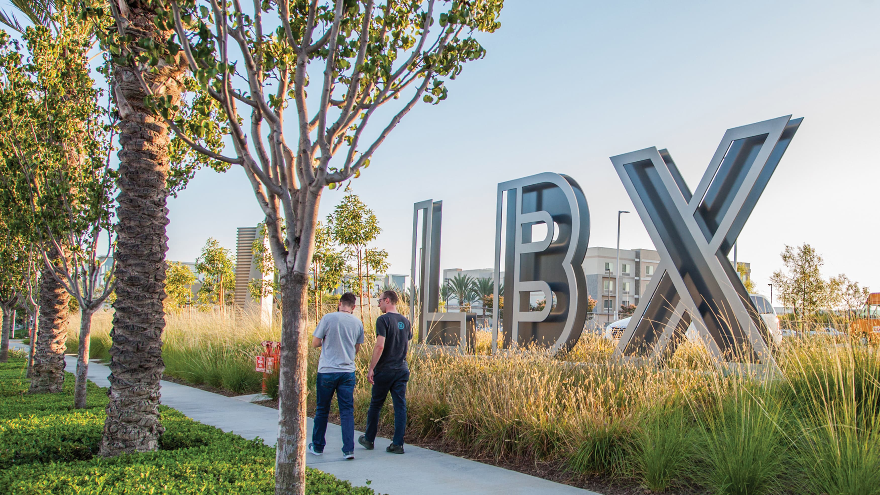 LBX large monument logo signage with people walking by