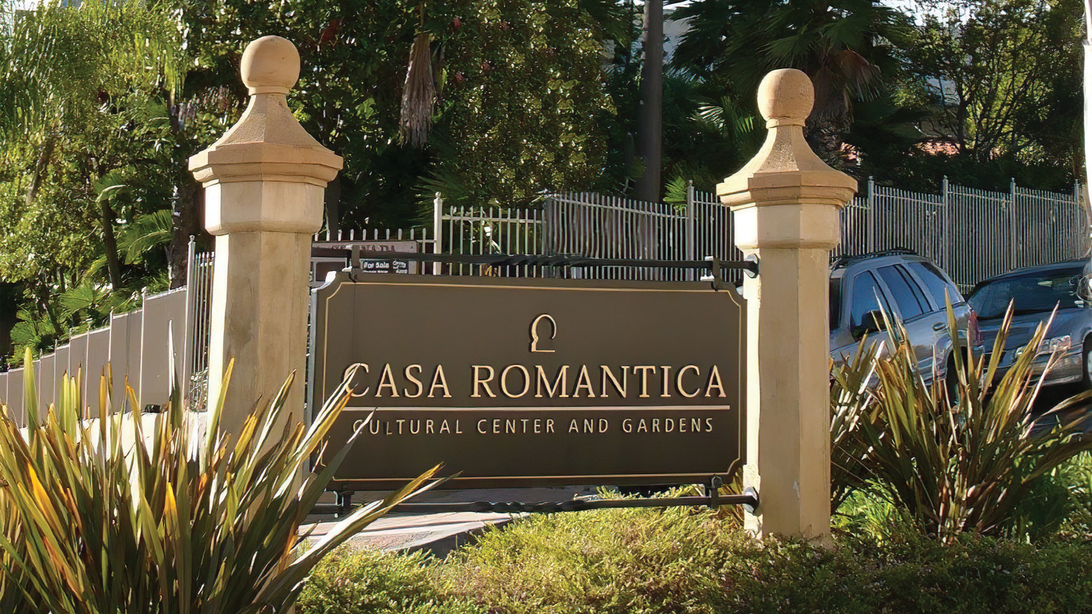 A photograph of a post and panel sign displaying Casa Romantica identity