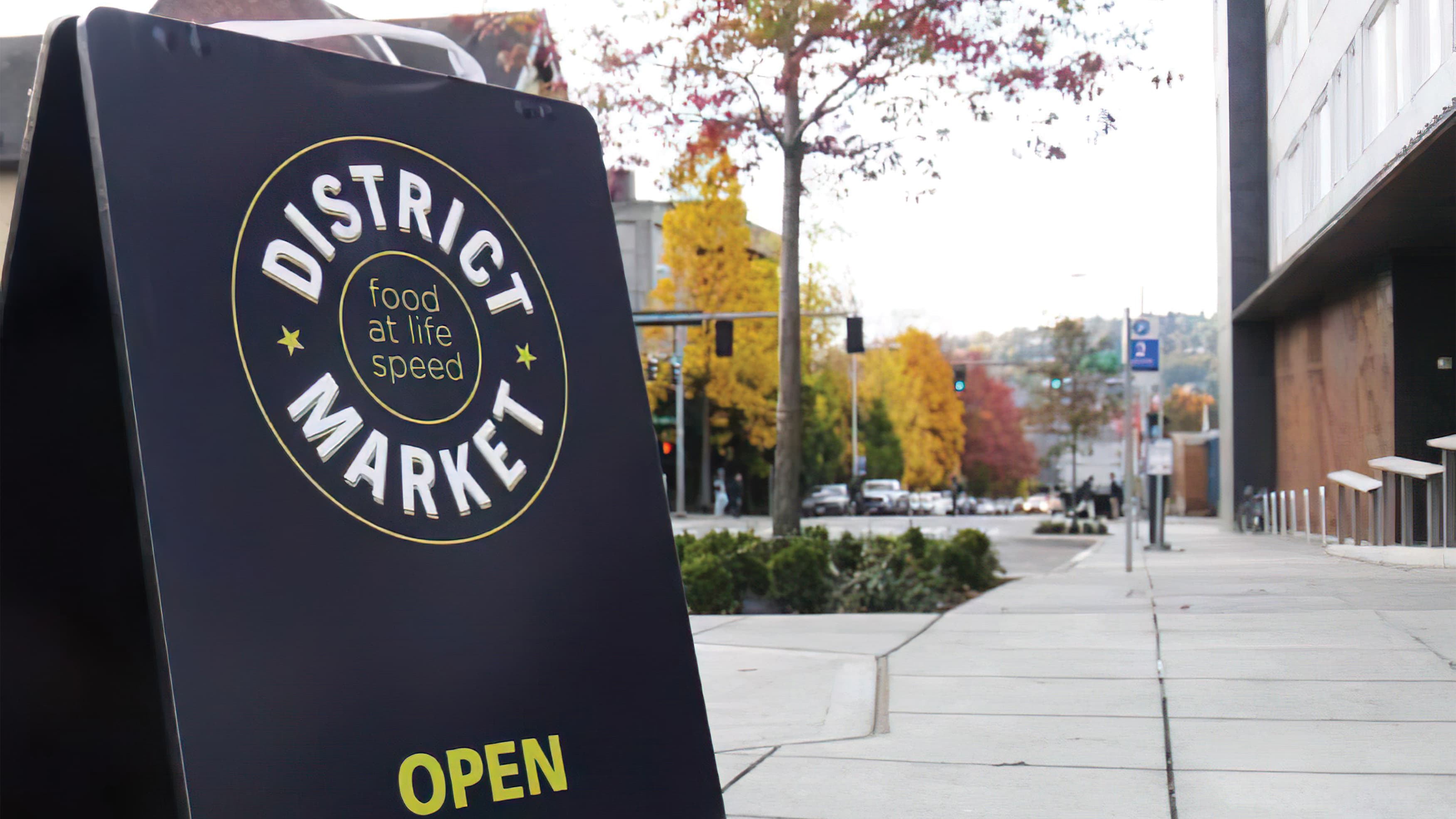 A photograph of an A-frame sign with District Market logo.
