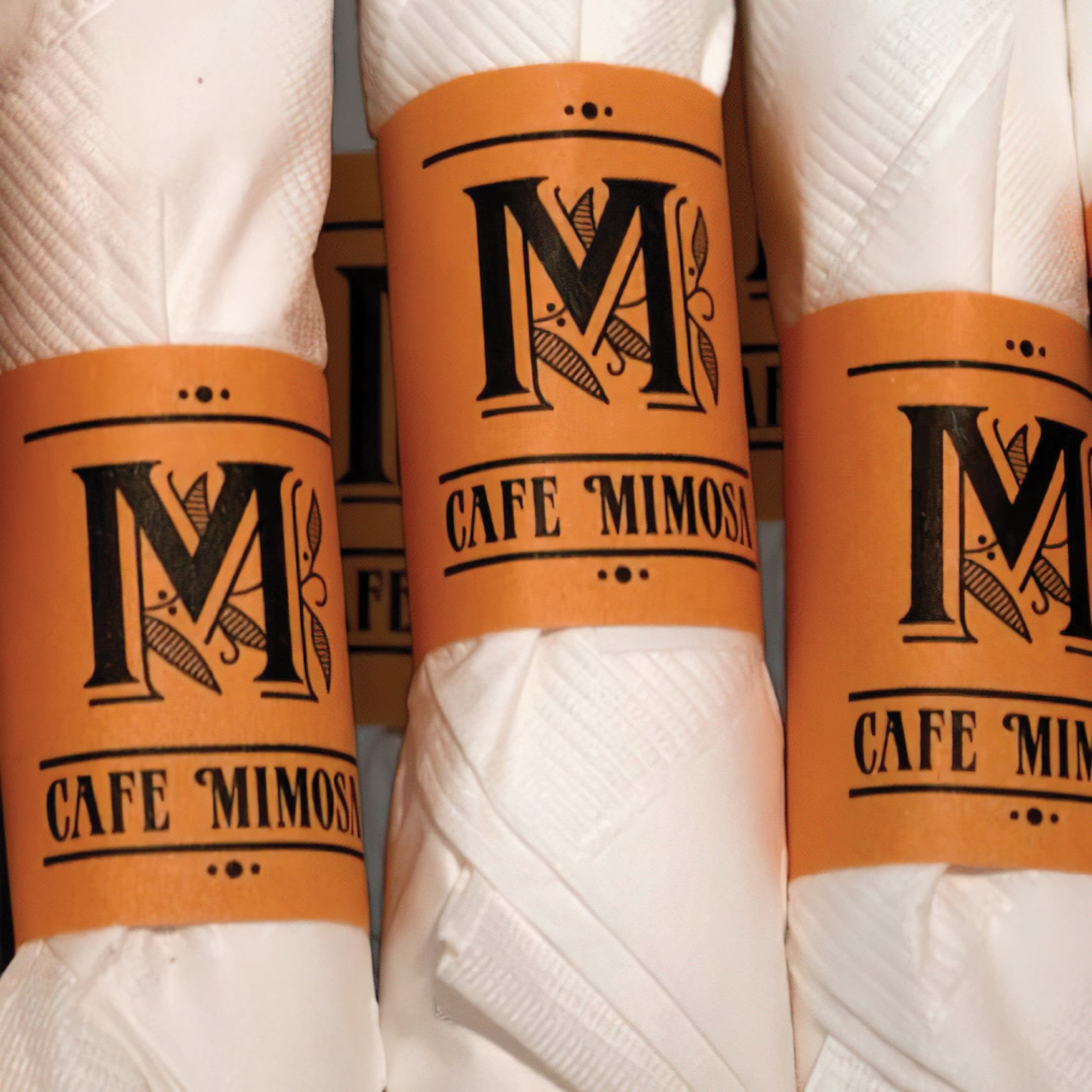 The Cafe Mimosa brand applied to a set of napkin bands.