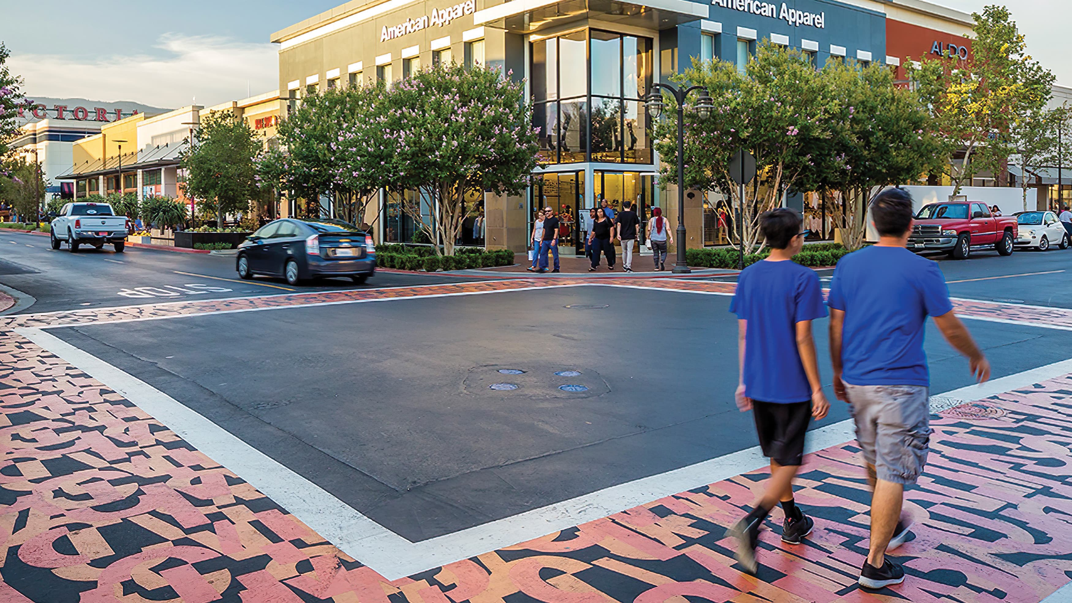 Father and son walk across custom designed crosswalk towards retail stores with background.