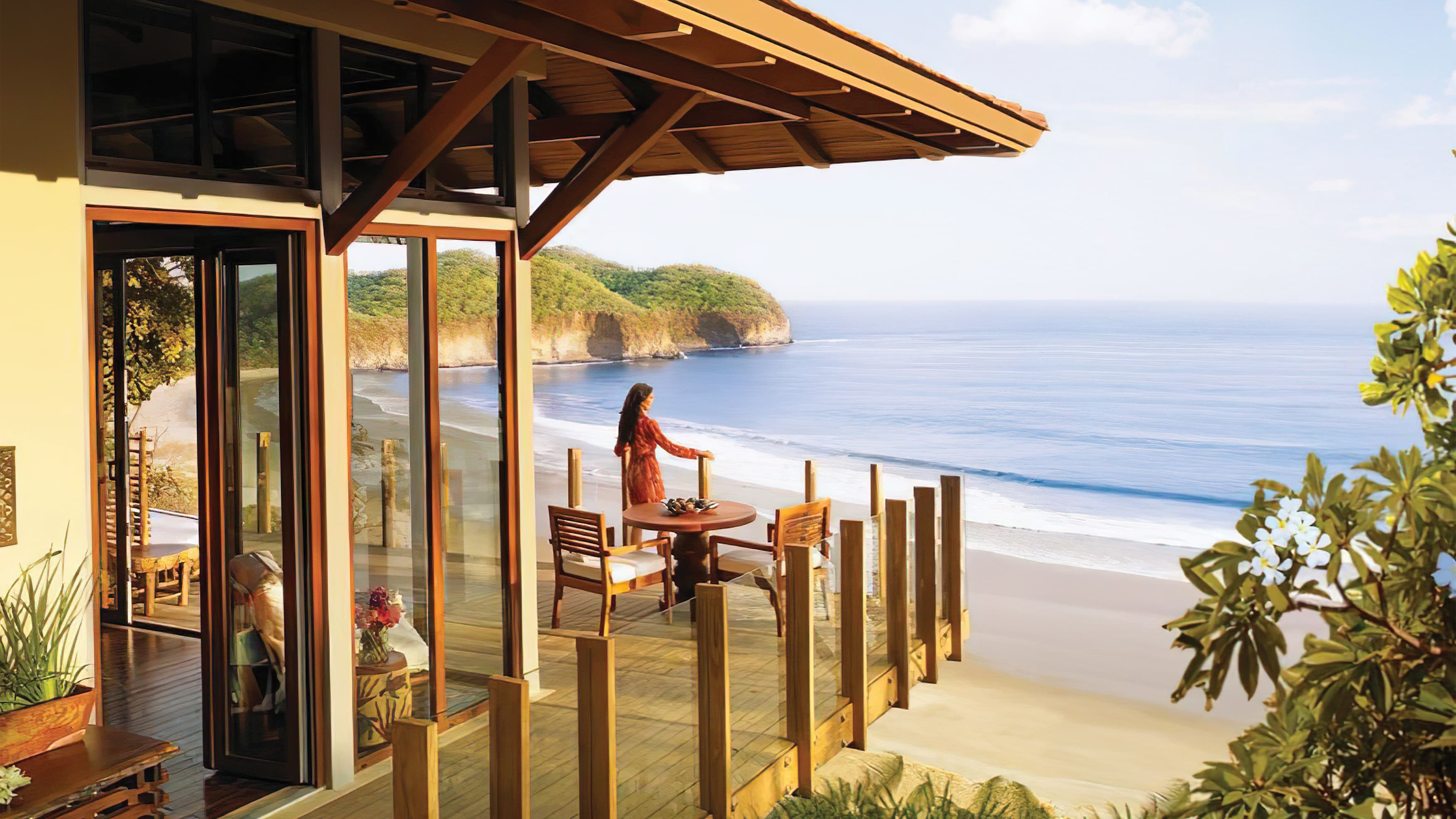 Woman stands on balcony overlooking beautiful tropical beach