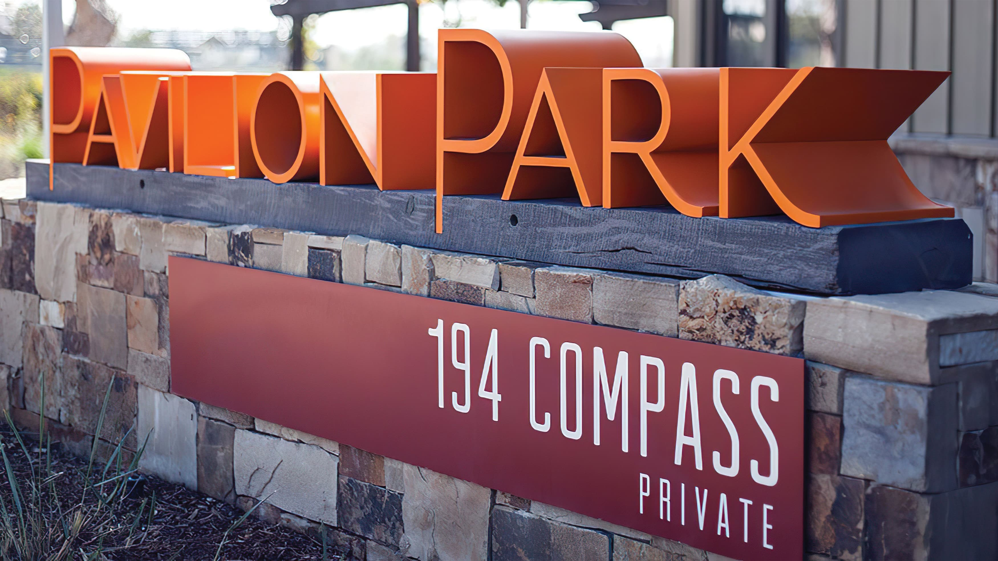 Low monument wall with park address applied to face and Pavilion Park identity on top