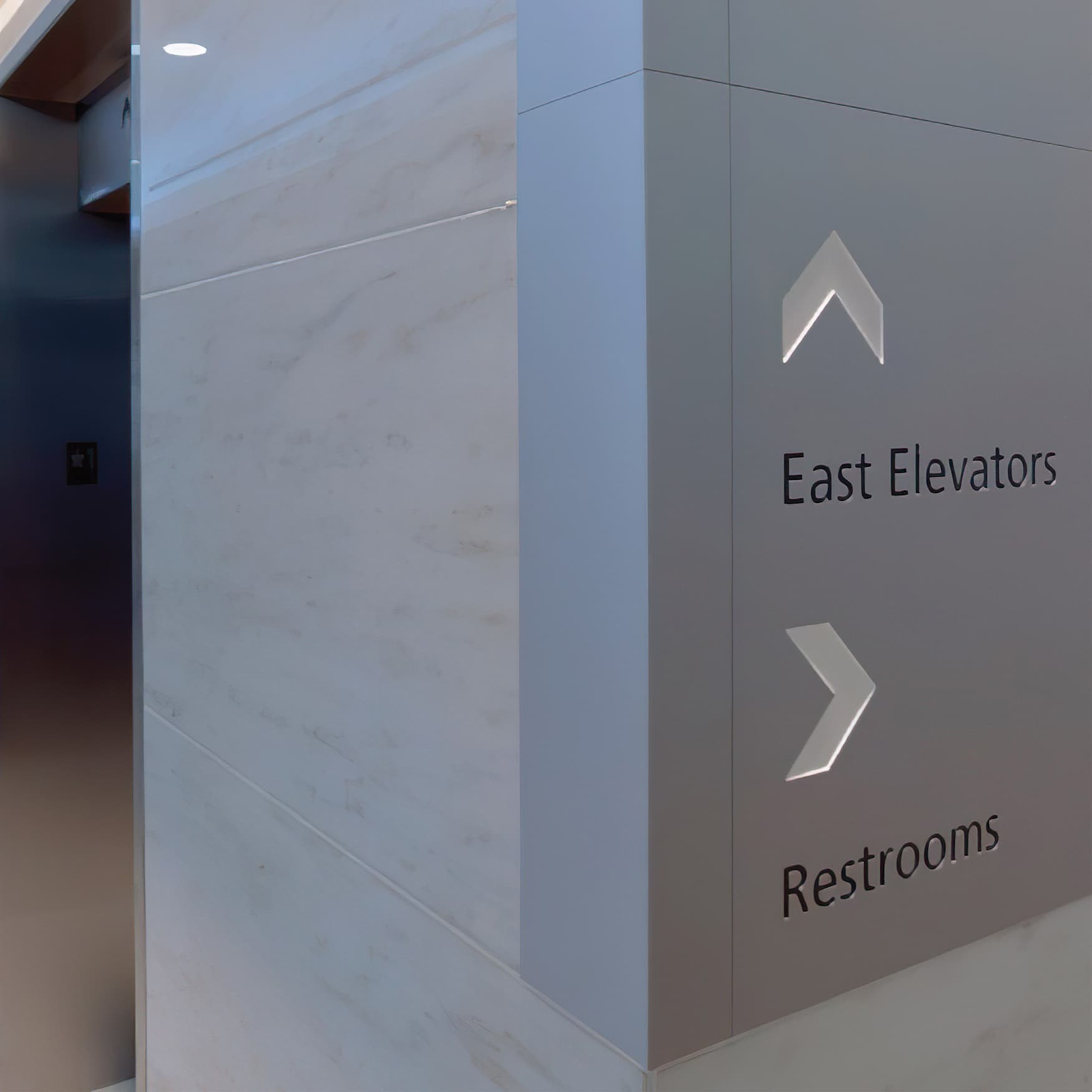 A photo of a wall mounted directional plaque located near an elevator.