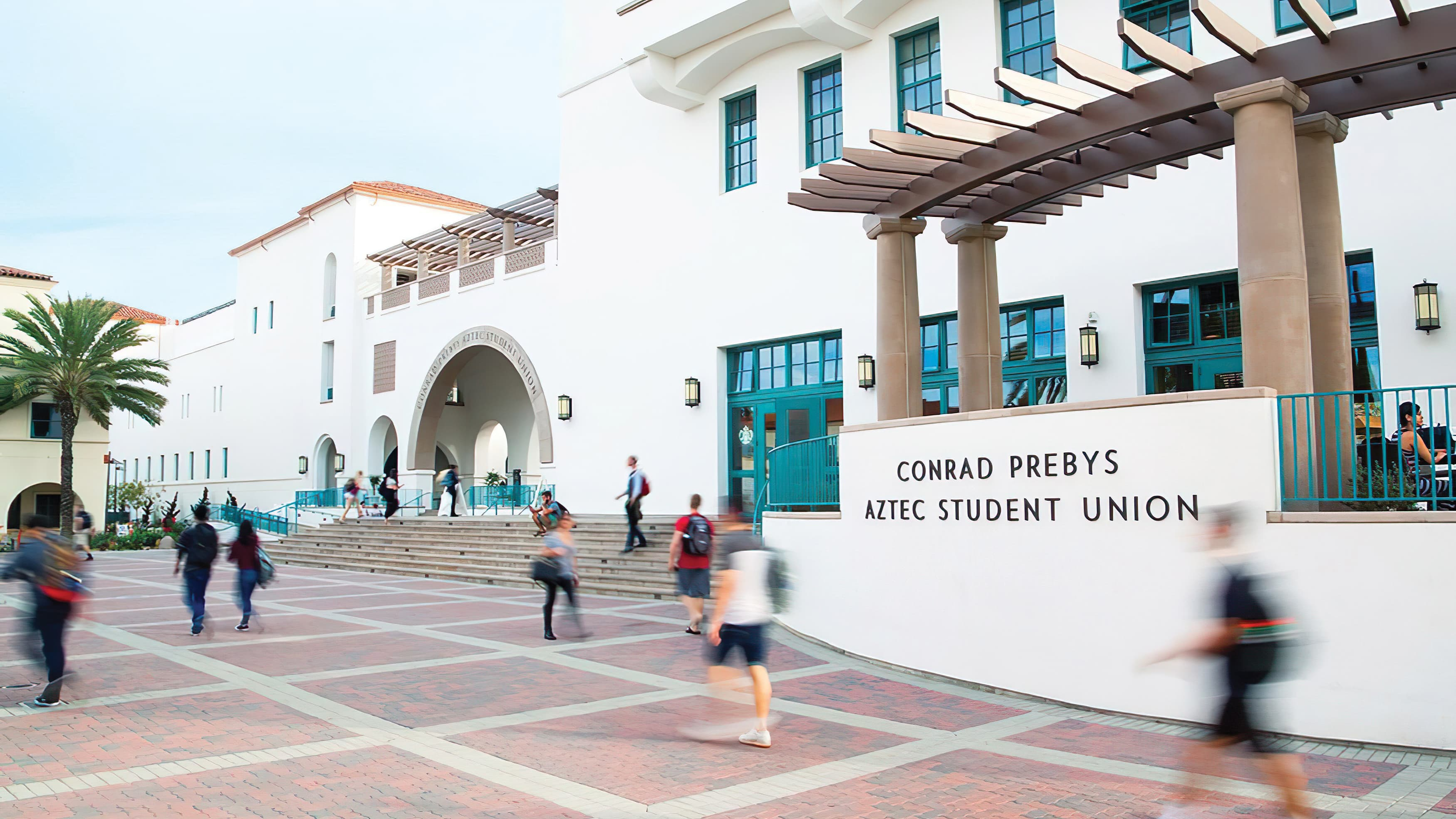 Students on campus walk past the student union identity mounted to the architecture