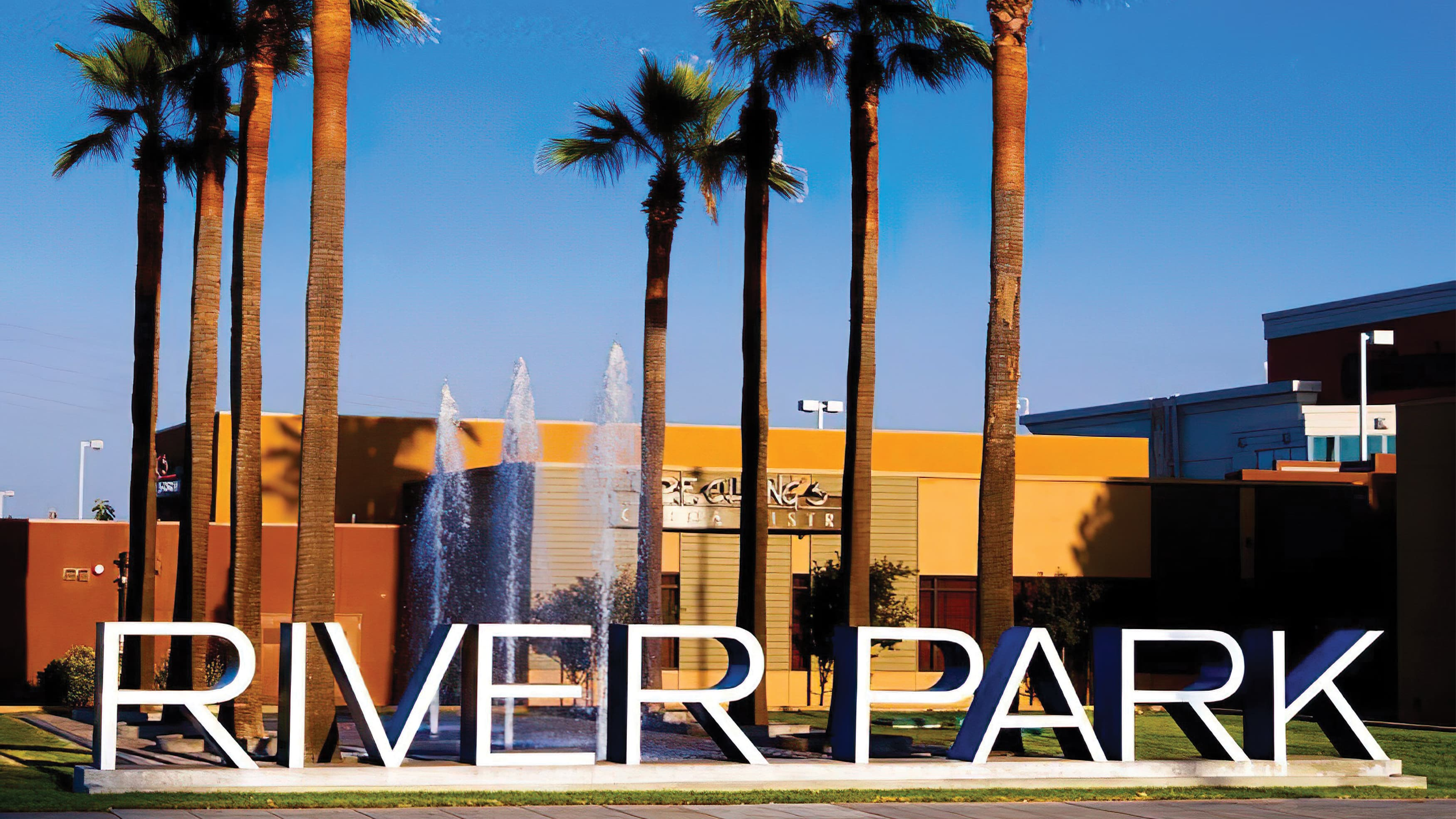 Large, dimensional Riverpark placemaking identity with white face and blue return flanked by a fountain and palm trees