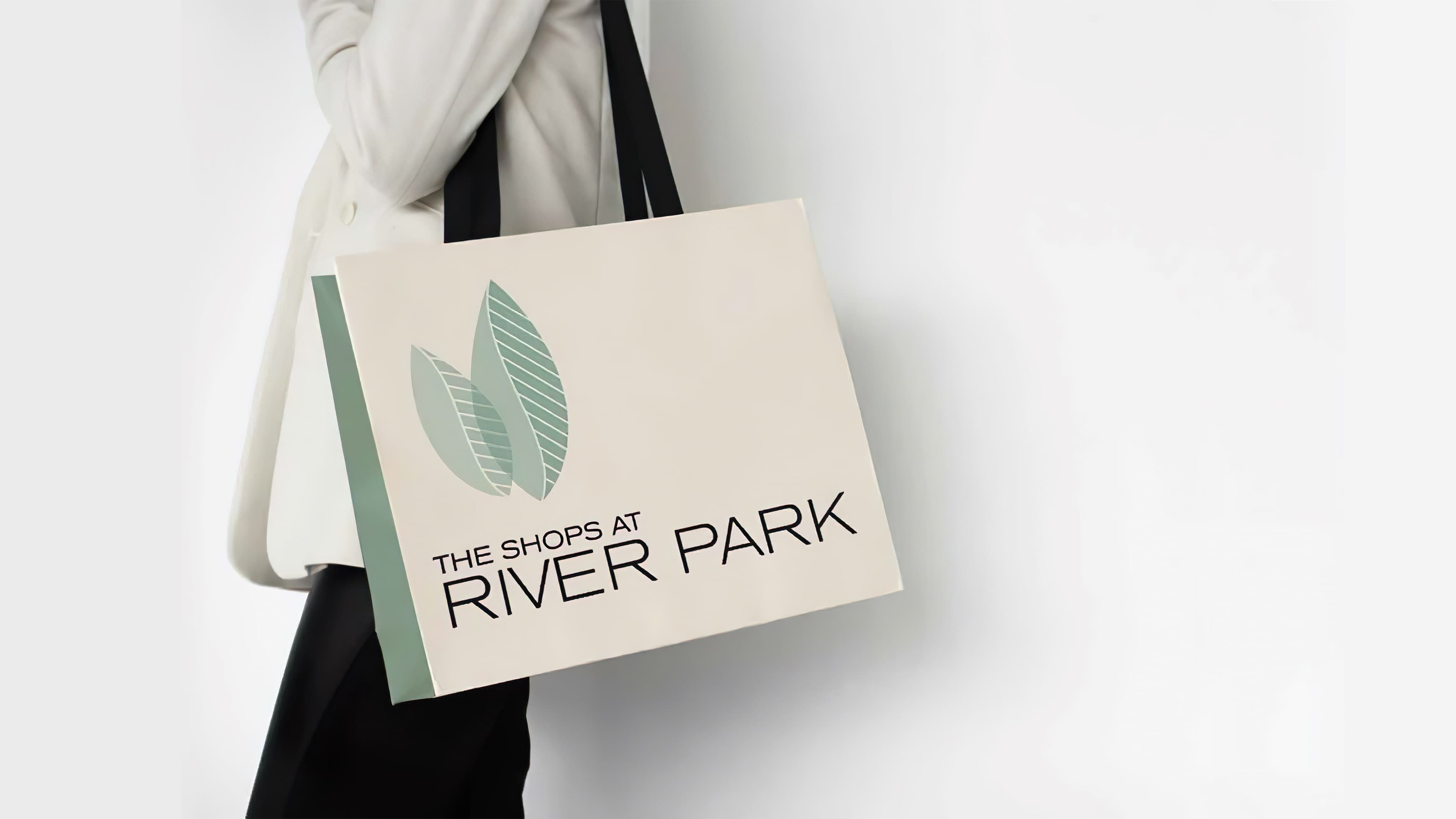 Woman holding a shopping bag branded with the Shops at River Park logo