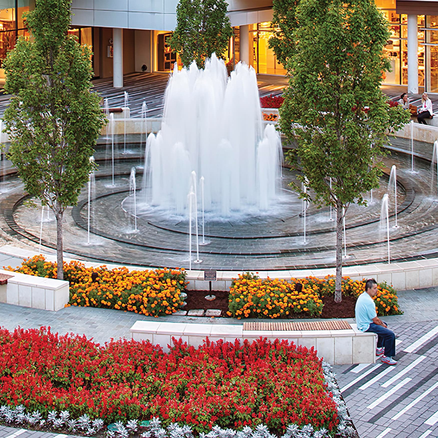Fountain in center of plaza with surrounding seating and integrated flowered landscaping