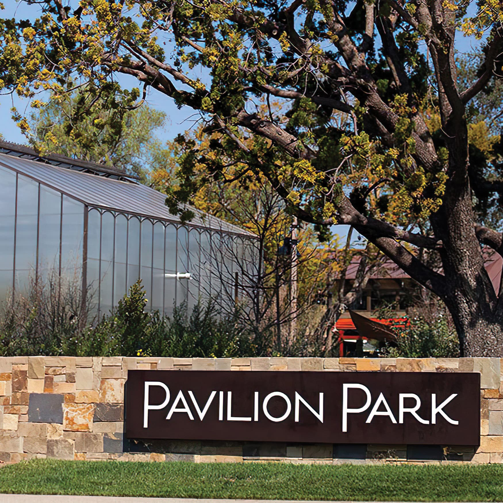 Monument identity stone wall with corten cabinet and Pavilion Park signage.
