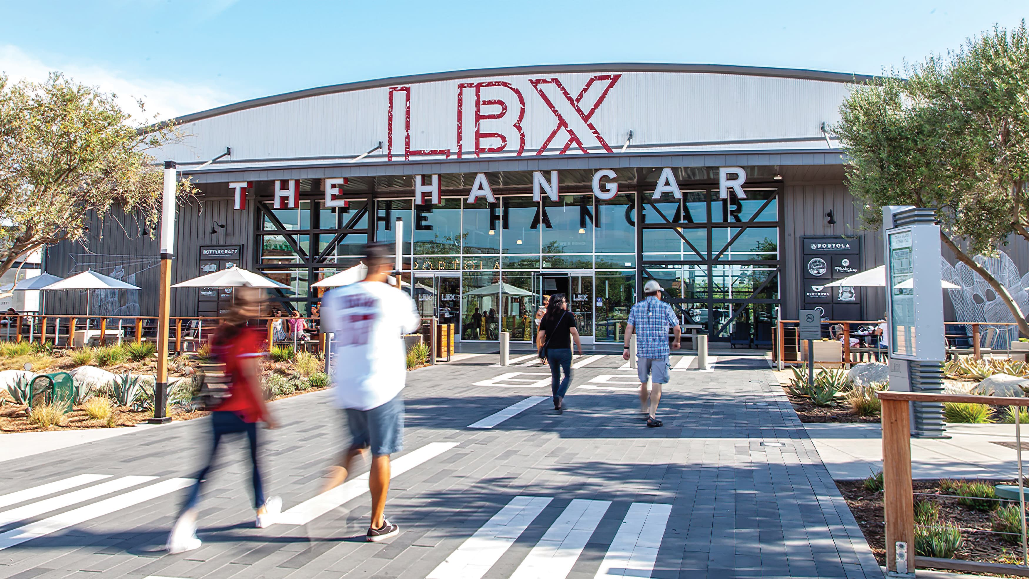 """People approach hangar style building with massive painted """"LBX"""" identity and dimensional """"The Hangar"""" channel letters"""