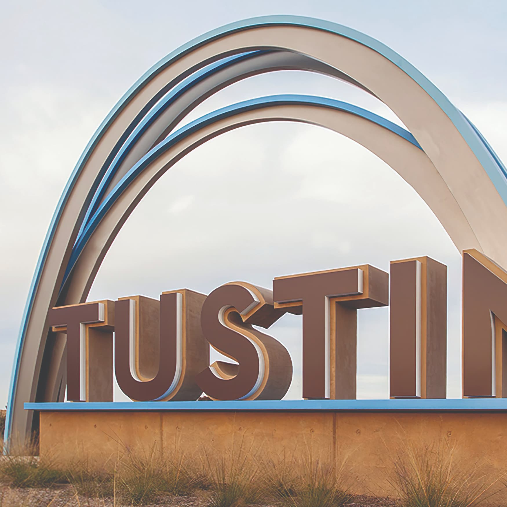 A photograph of a monument sign at Tustin Legacy featuring an arch and large fabricated letters.