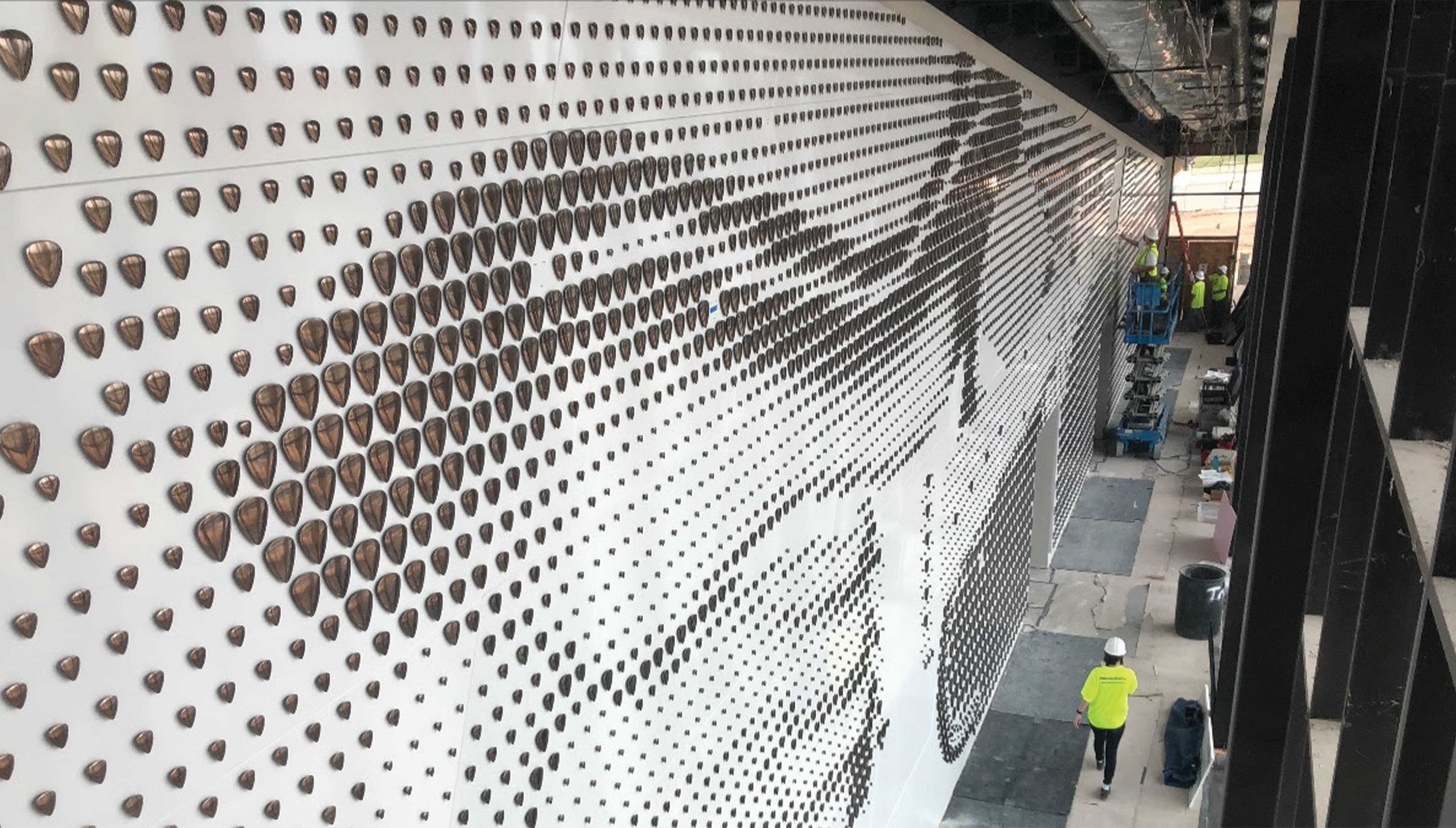 Detail of guitar pick specialty graphics being installed on donor wall of Buddy Holly Hall in Dallas, TX