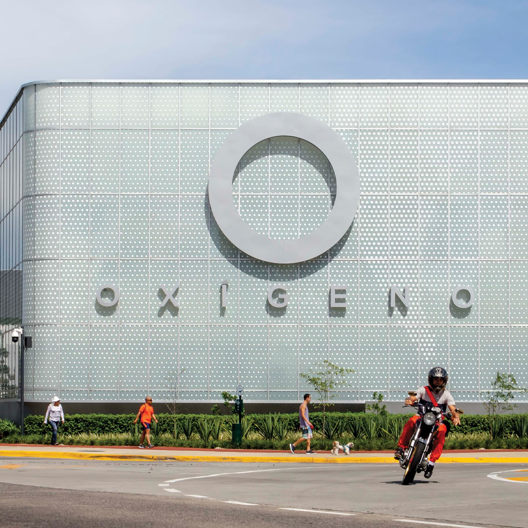 Oxigeno Retail building facade signage in the background as motorcycle rides in front