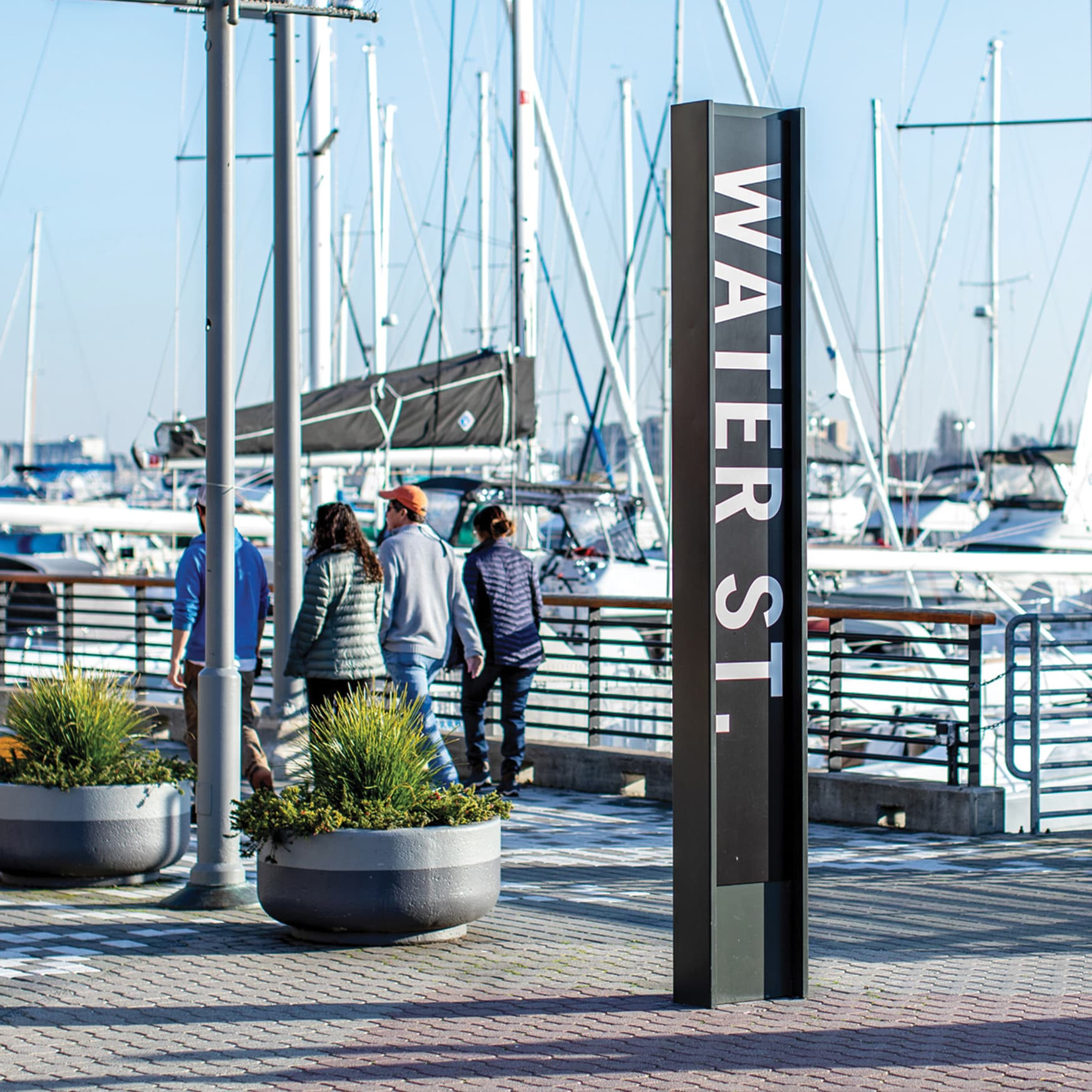 Waterfront wayfinding signage on the boardwalk with boats docked in the background