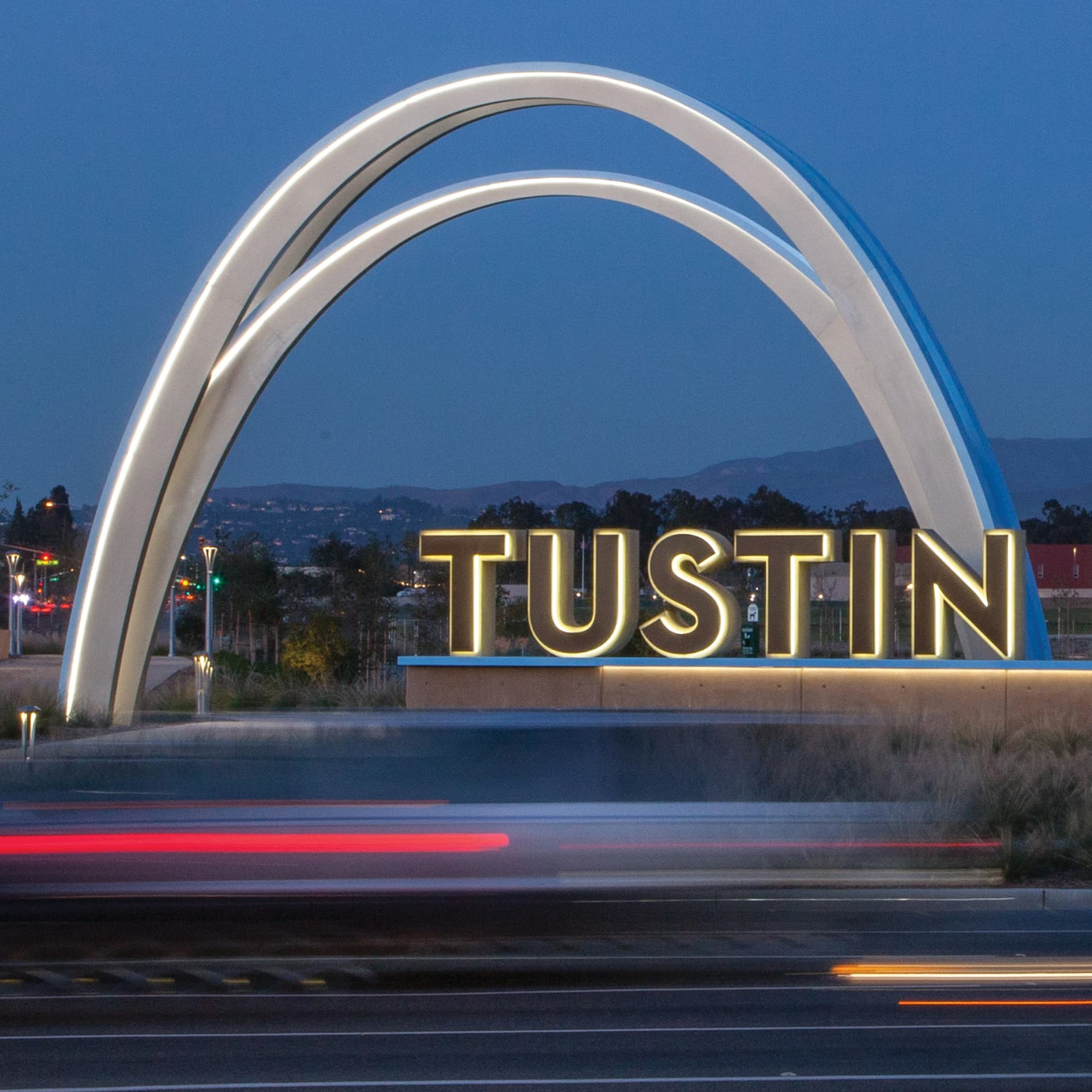 Tustin Legacy monument signage illuminated at night with cars driving by in foreground