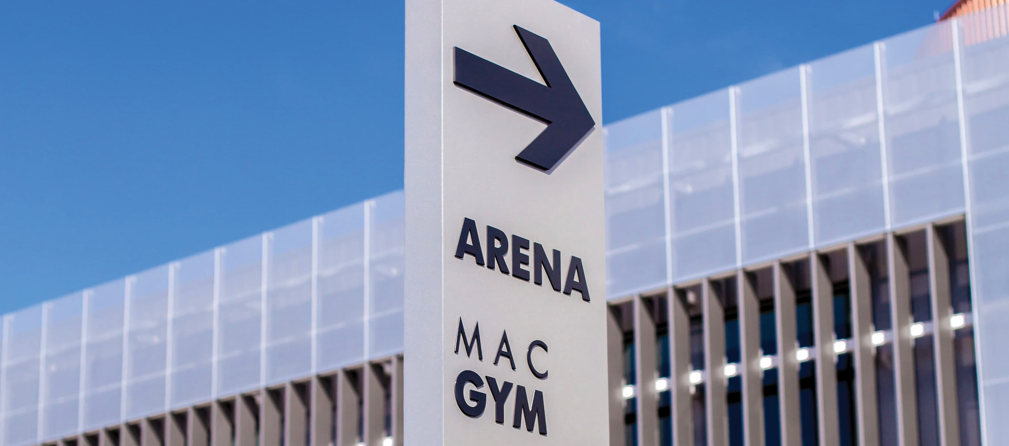 ARROW ON SIGN POINTING TO NEARBY ARENA IN BACKGROUND
