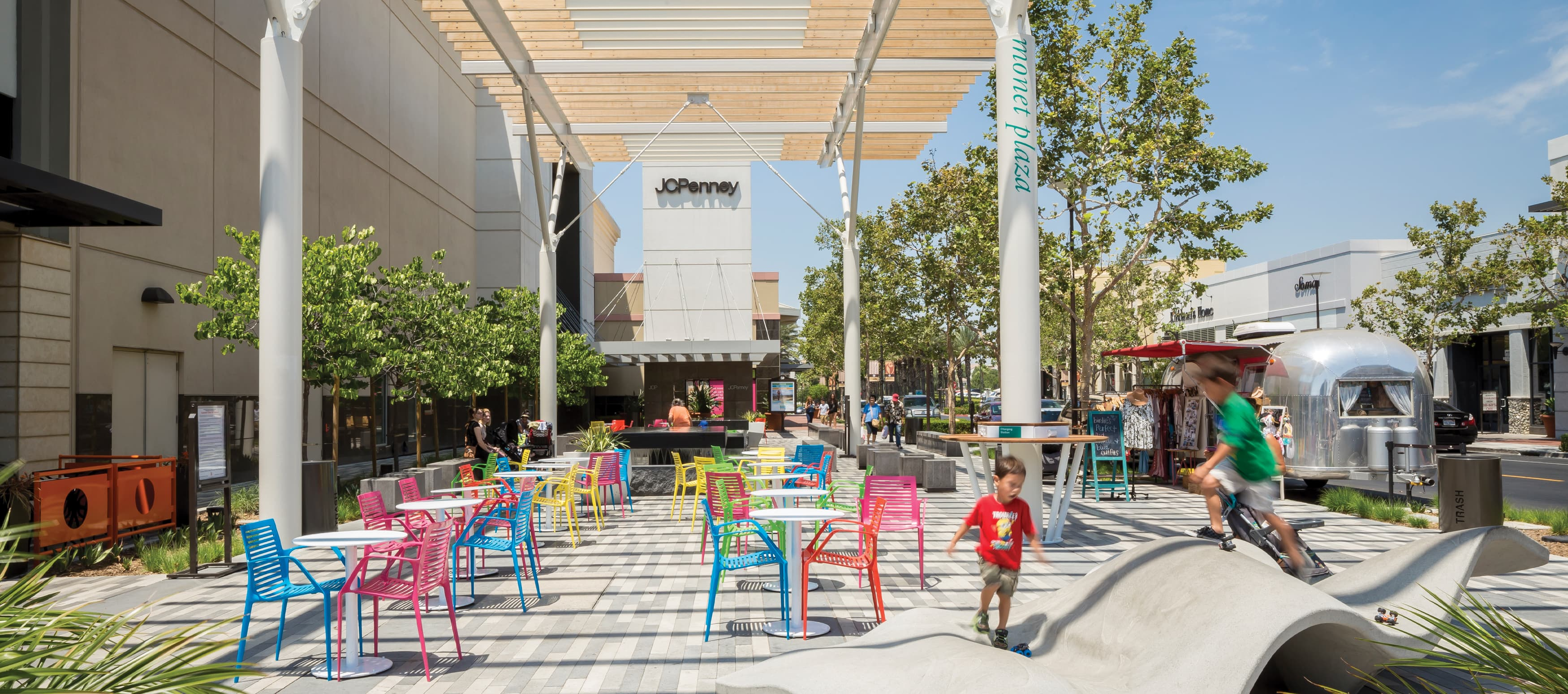 children play on sculptural piece at outdoor retail center with colorful chairs and shopping in the background