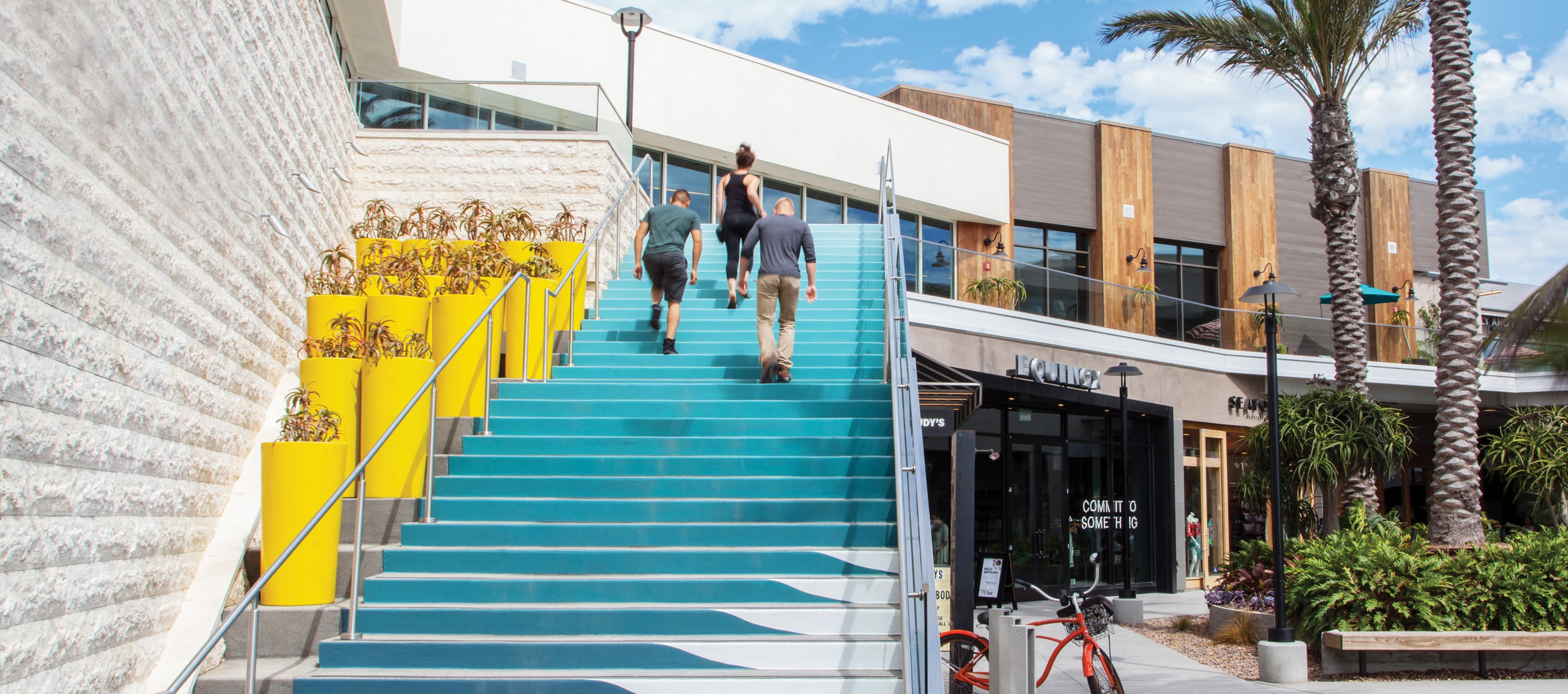A group of people walk up a flight of stairs painted shades of blue to mimic ocean waves at an outdoor retail center