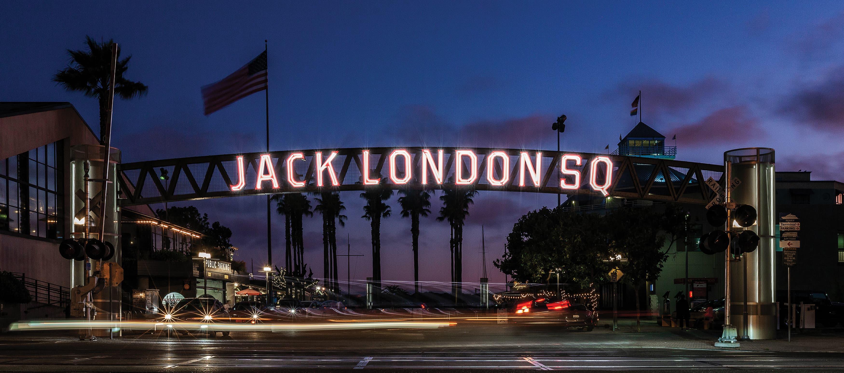 illuminated overhead street sign at night behind railroad tracks