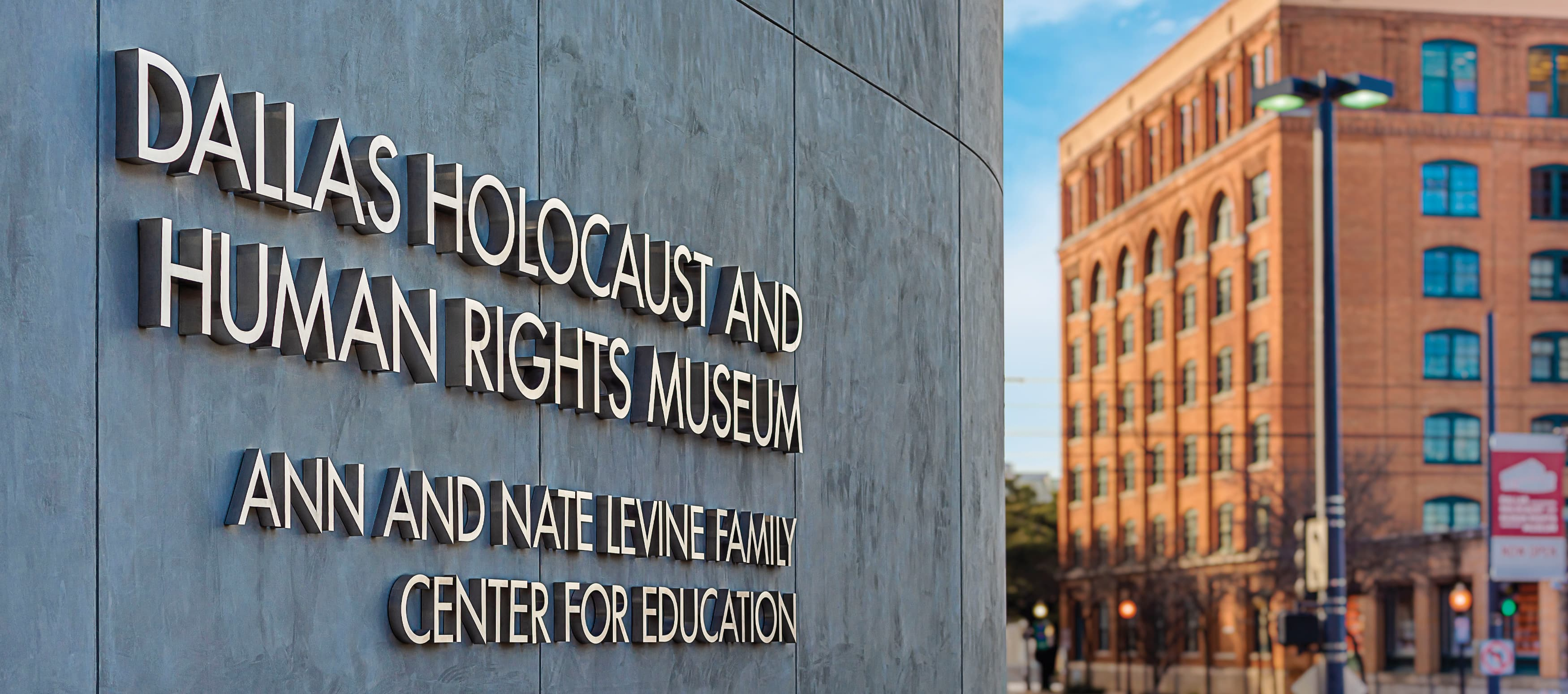 Entrance sign outdoors to the Dallas Holocaust Museum with city buildings in background