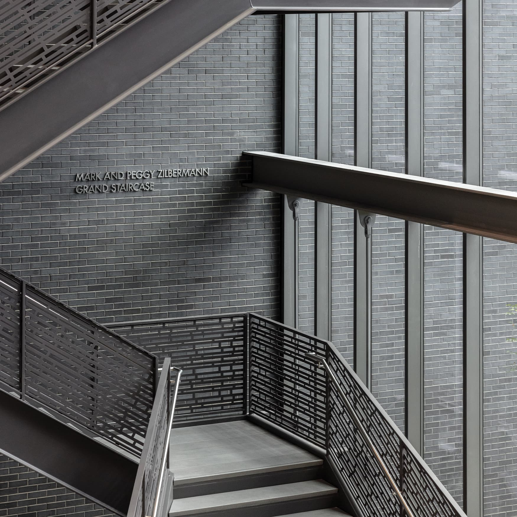 Interior Mark & Peggy Zilbermann grand staircase signage design at The Dallas Holocaust and Human Rights Museum