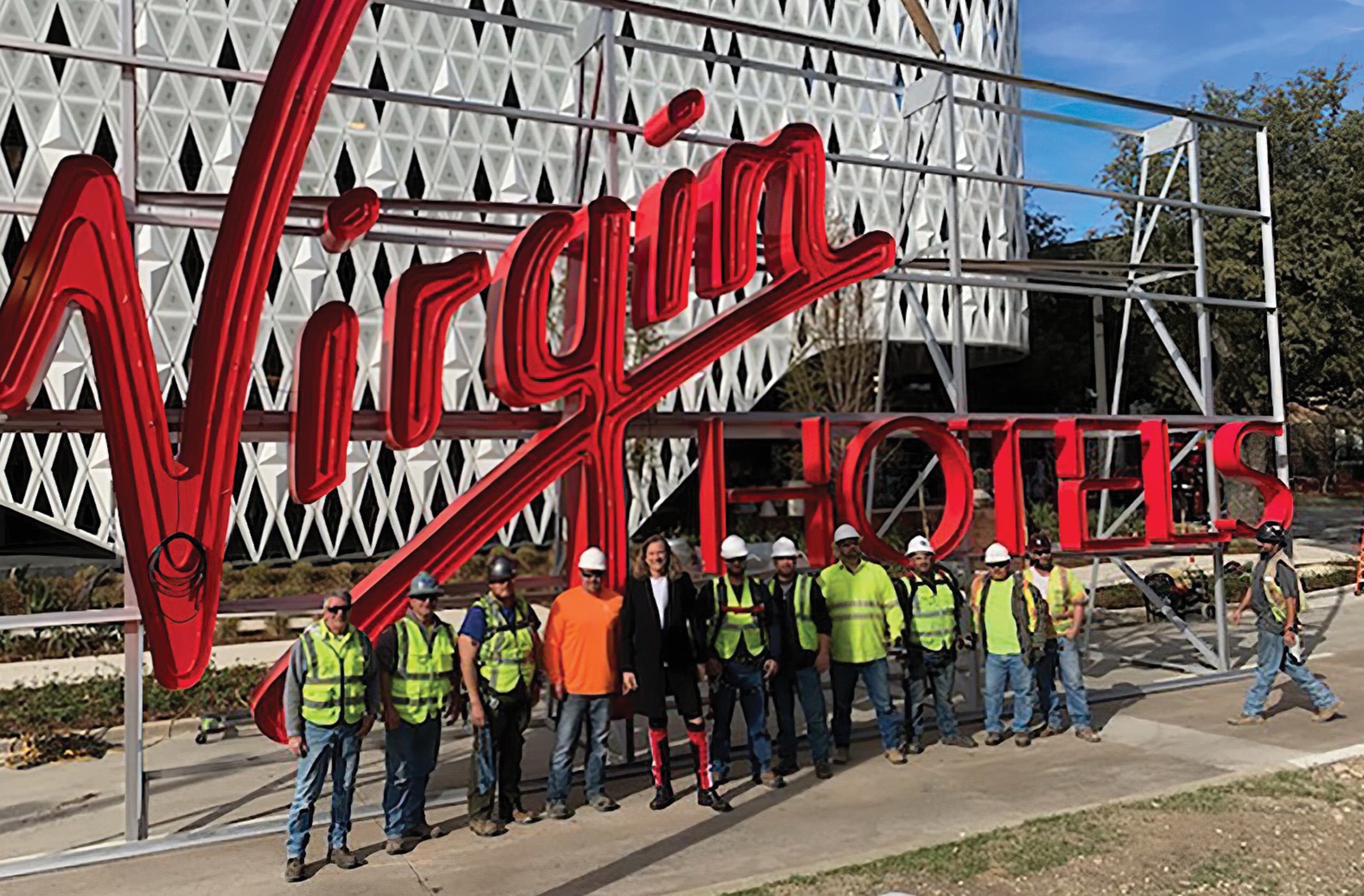 A photograph of a large fabricated sign for the new Virgin hotel featuring the installation team.