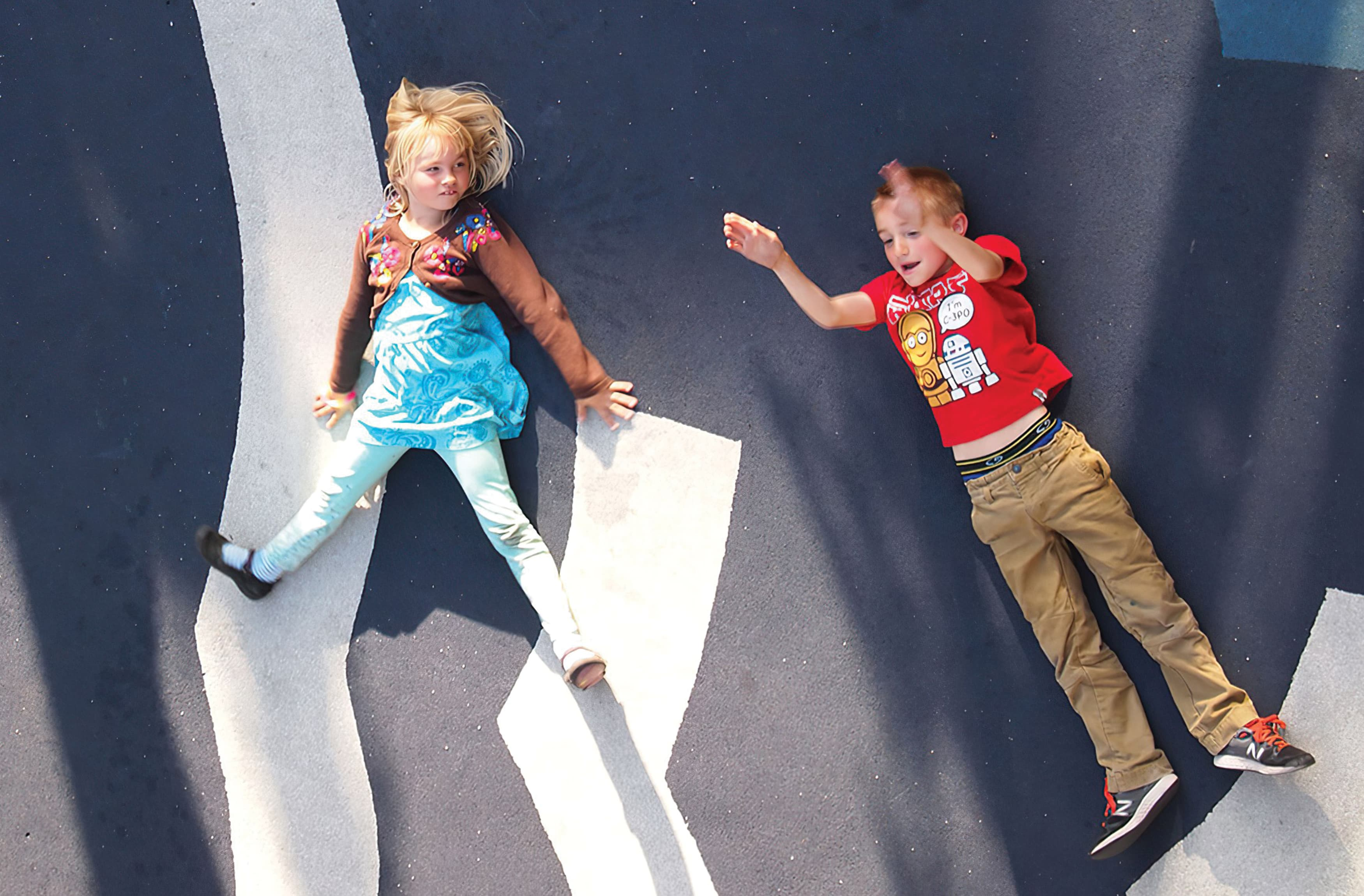 Children playing in an area with painted pavement graphics.