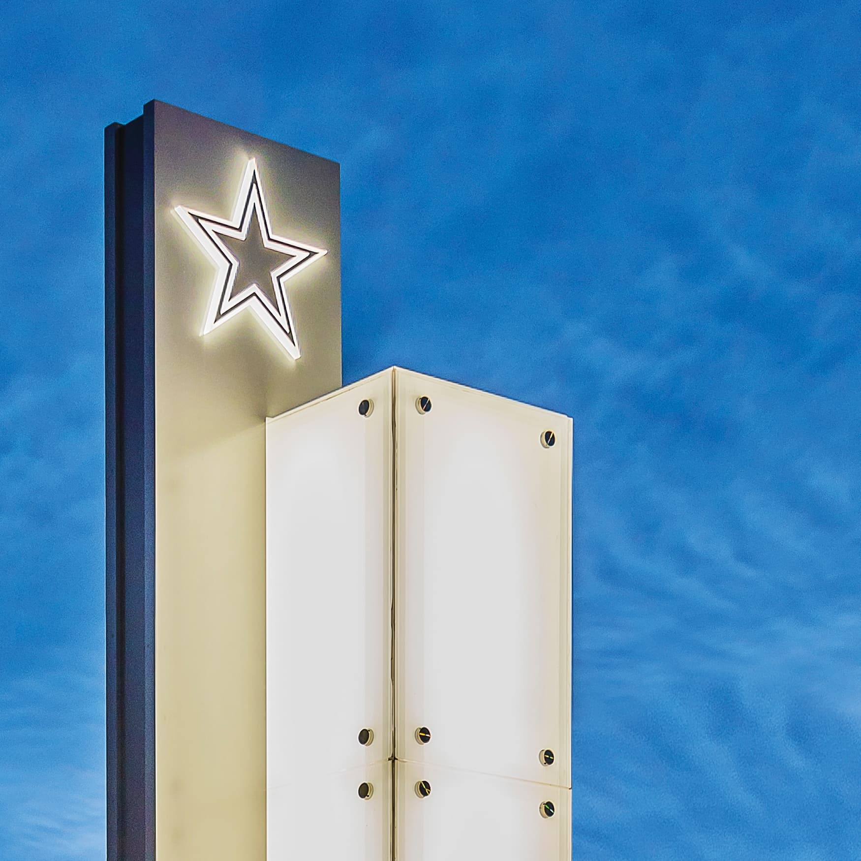 Dallas Cowboys logo illuminated pylon signage at dusk