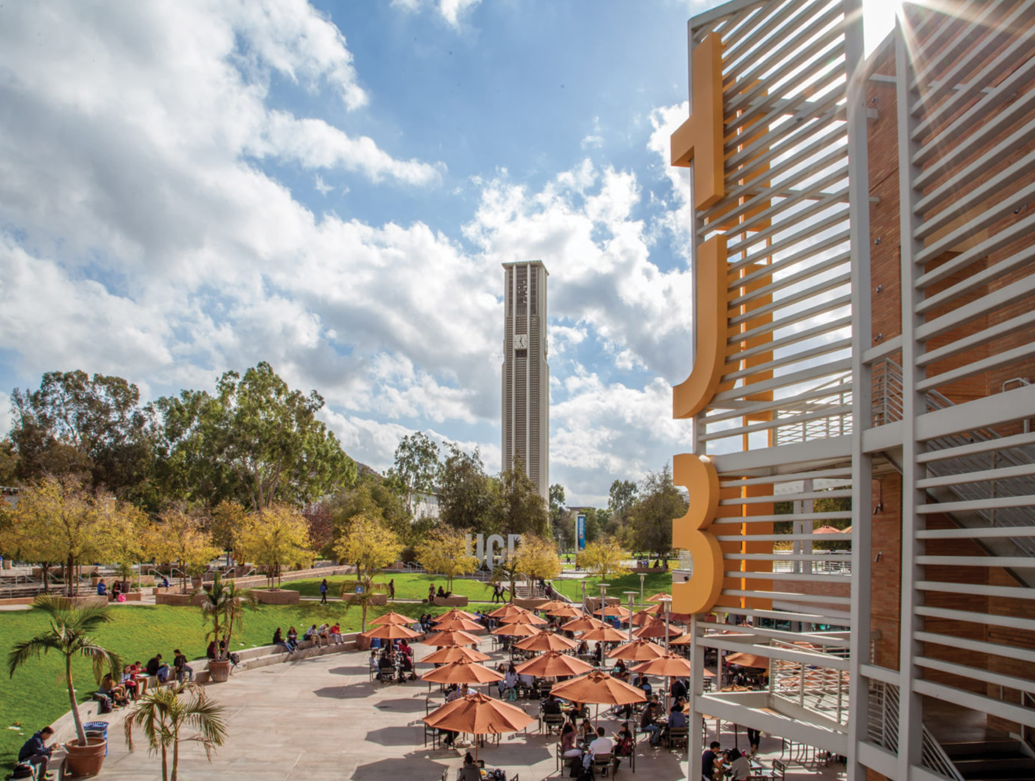 A plaza featuring signage and open-air seating on the campus of UCR.