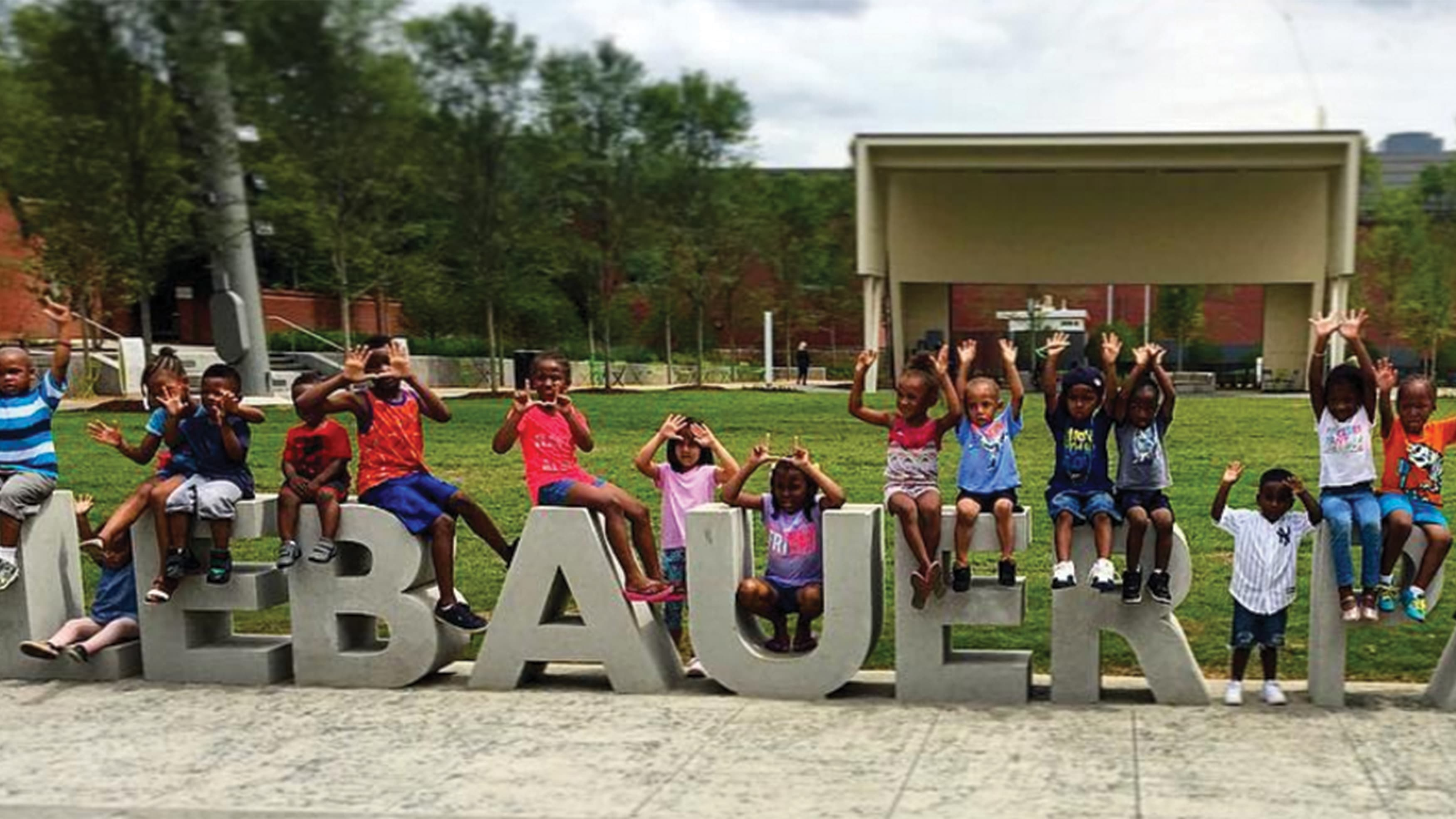 Kids gather in front of monument sign for LeBauer Park