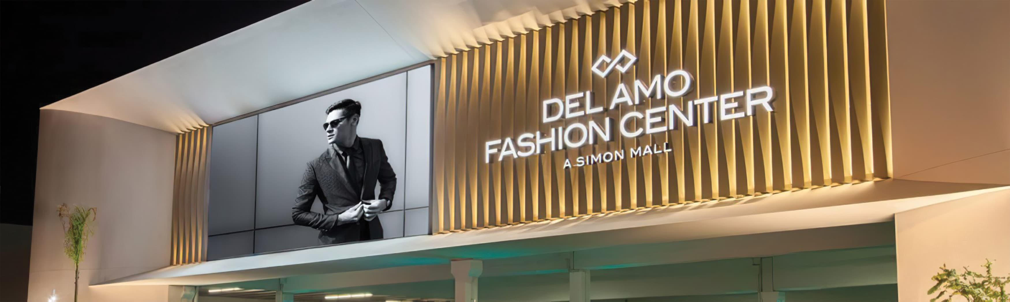 A nighttime image featuring an illuminated channel letter sign and a lifestyle graphic, both mounted on an architectural facade at Del Amo Fashion Center.