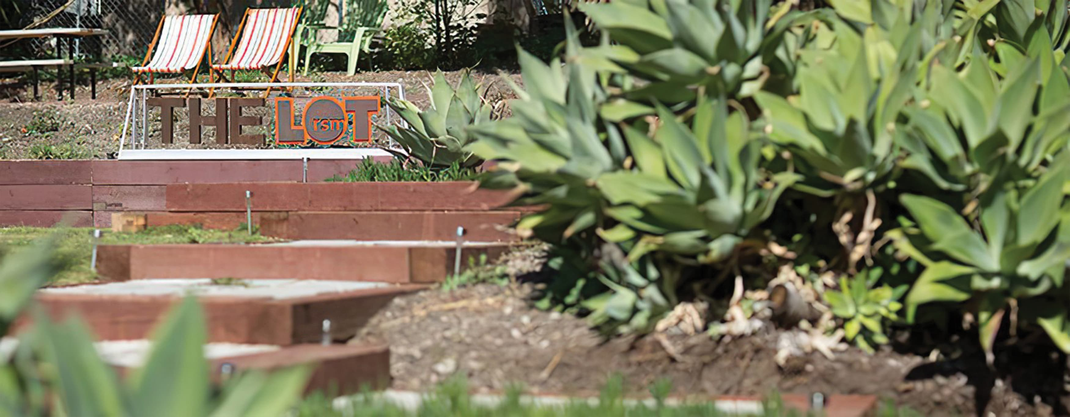 An outdoor space featuring a fabricated sign, seating, and succulent vegetation.