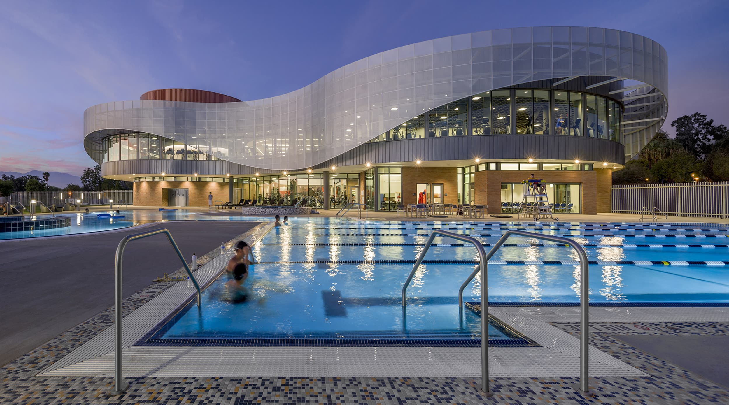 People swimming in an outdoor pool at night at a college recreation center