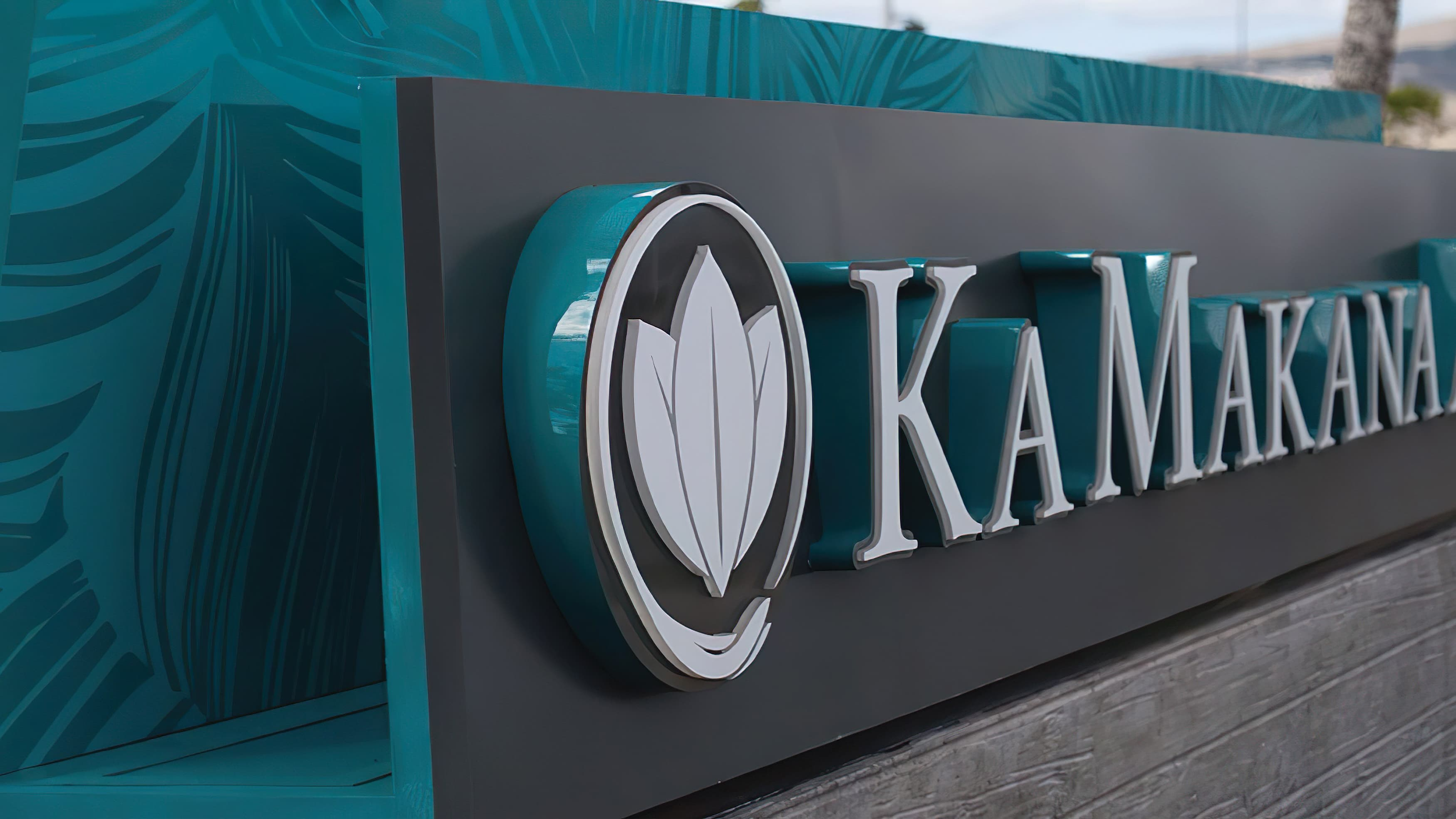 Monument signage at Ka Makana in Hawaii with tone on tone pattern and colored letter returns