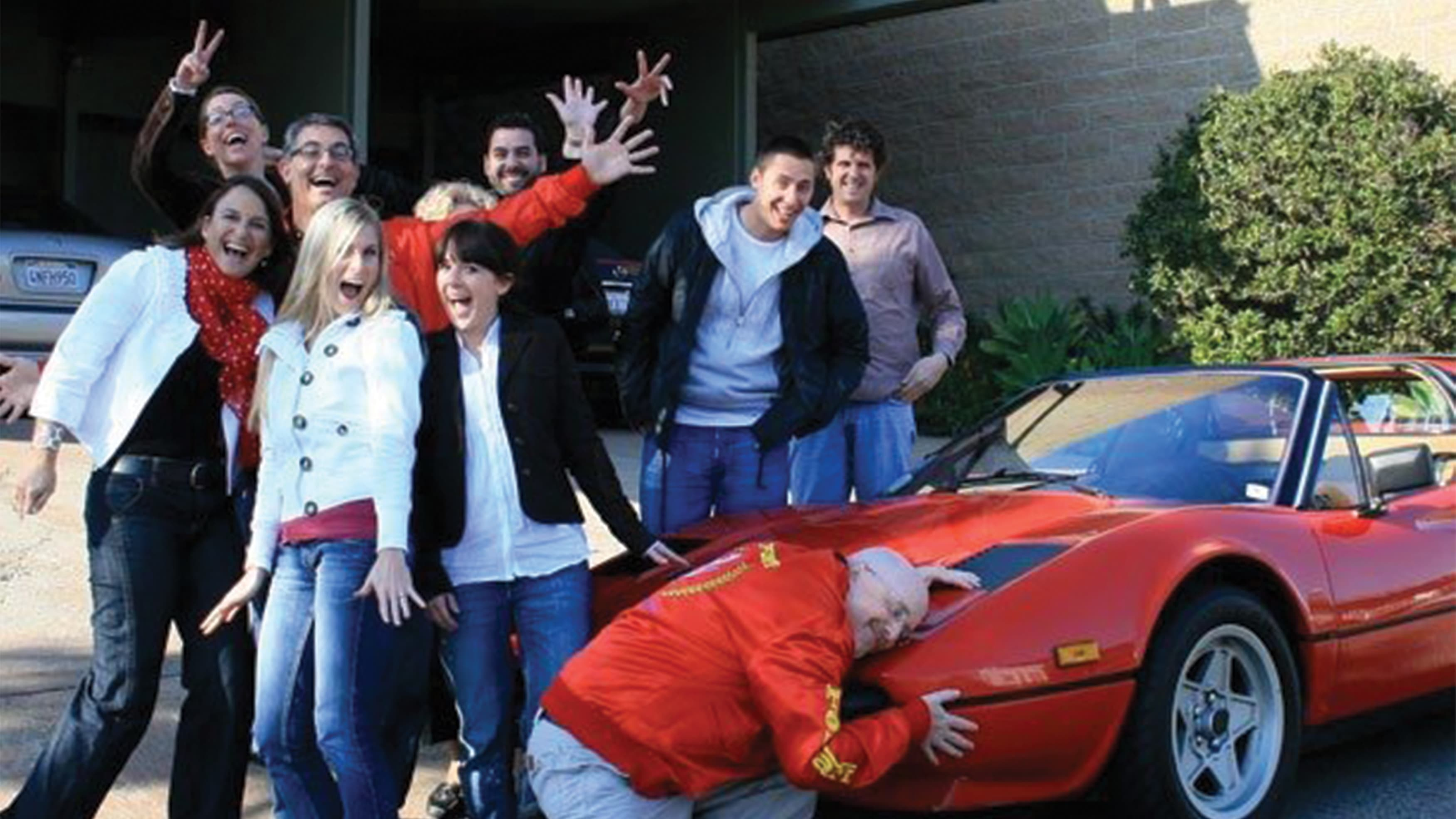 RSM team members gather around a red Ferrari to send off Harry and Martin on their trip to Abu Dhabi