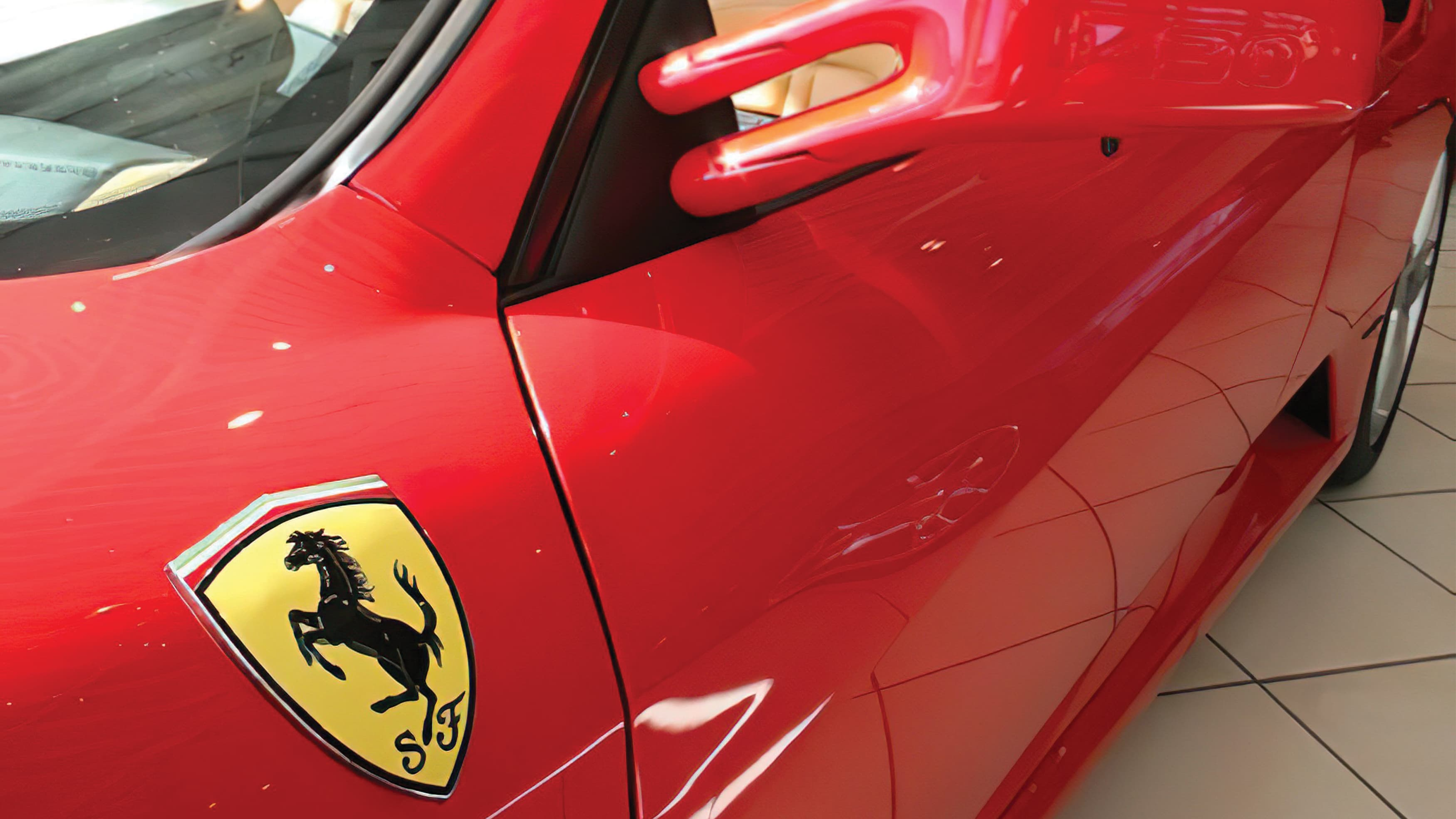 Detail photograph of a red ferrari with the classic Ferrari racing badge.