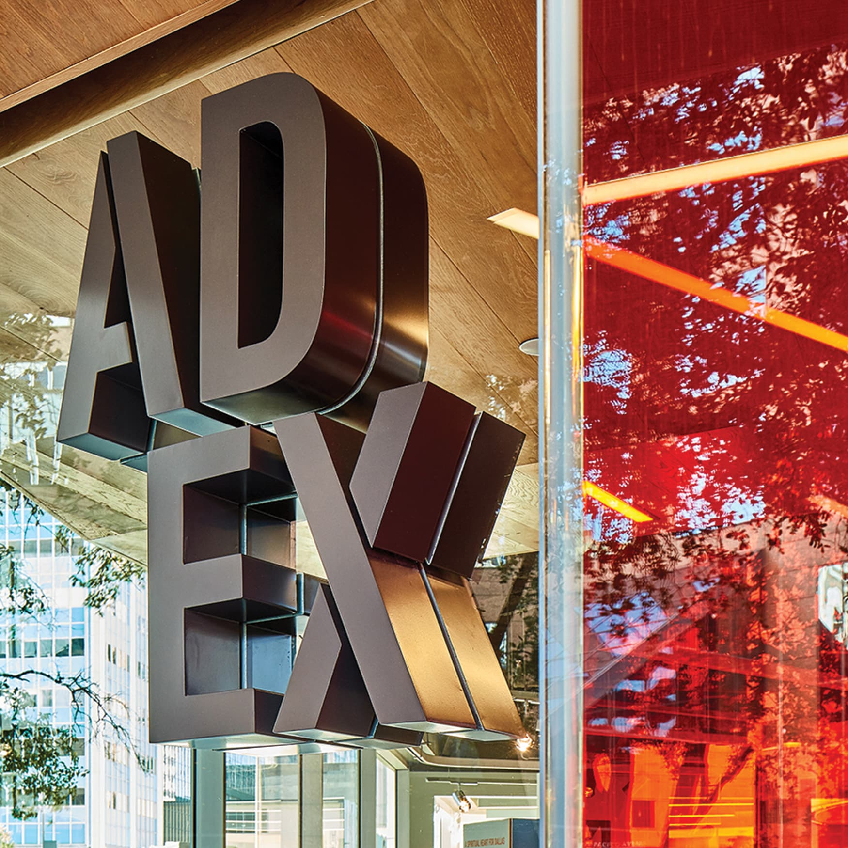 AD EX dimensional signage identity mounted to glass facade of architecture