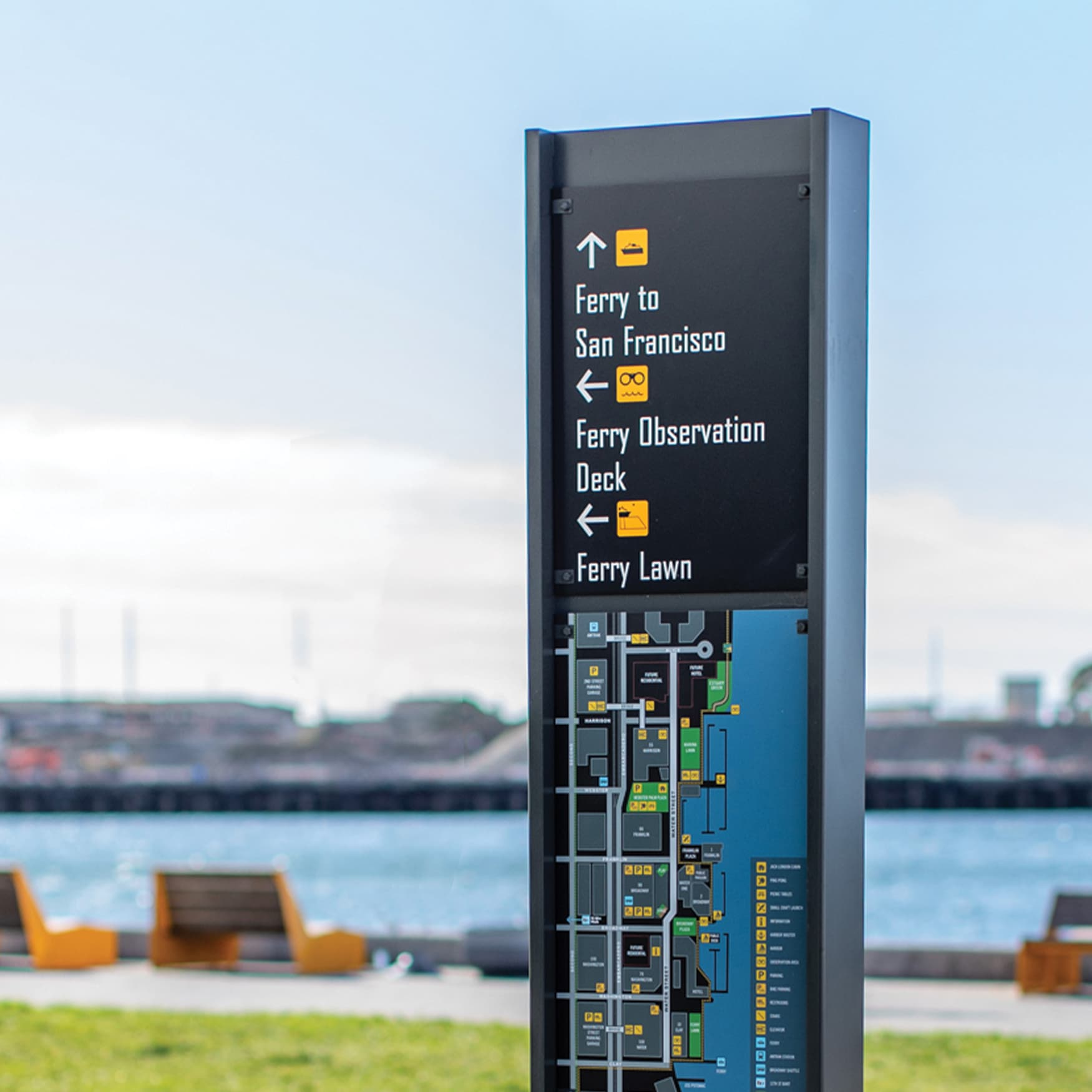 Waterfront Wayfinding Signage with Oakland Harbor and waterfront seating in the background