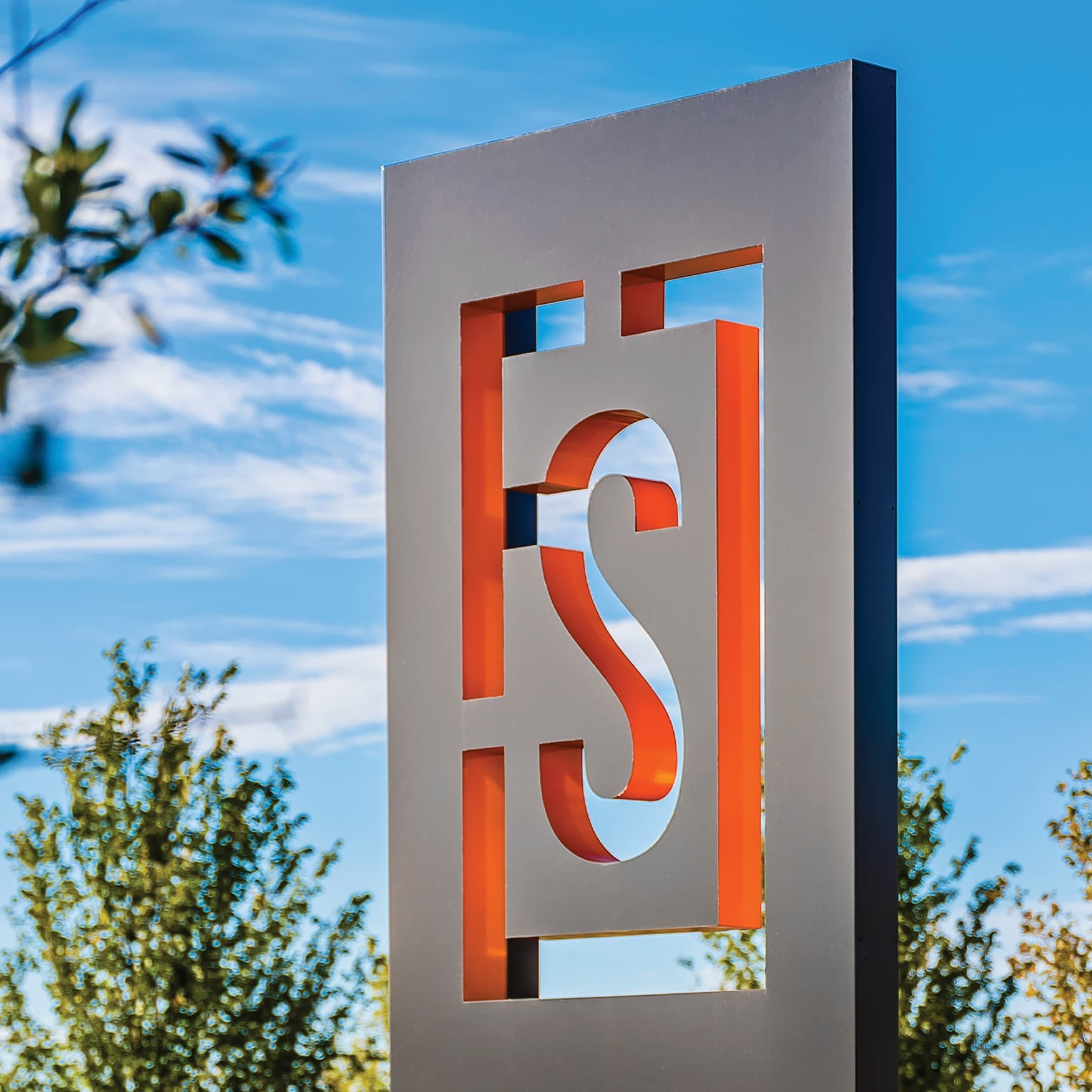 Detail of orange and black monument signage with painted returns at Frisco Station