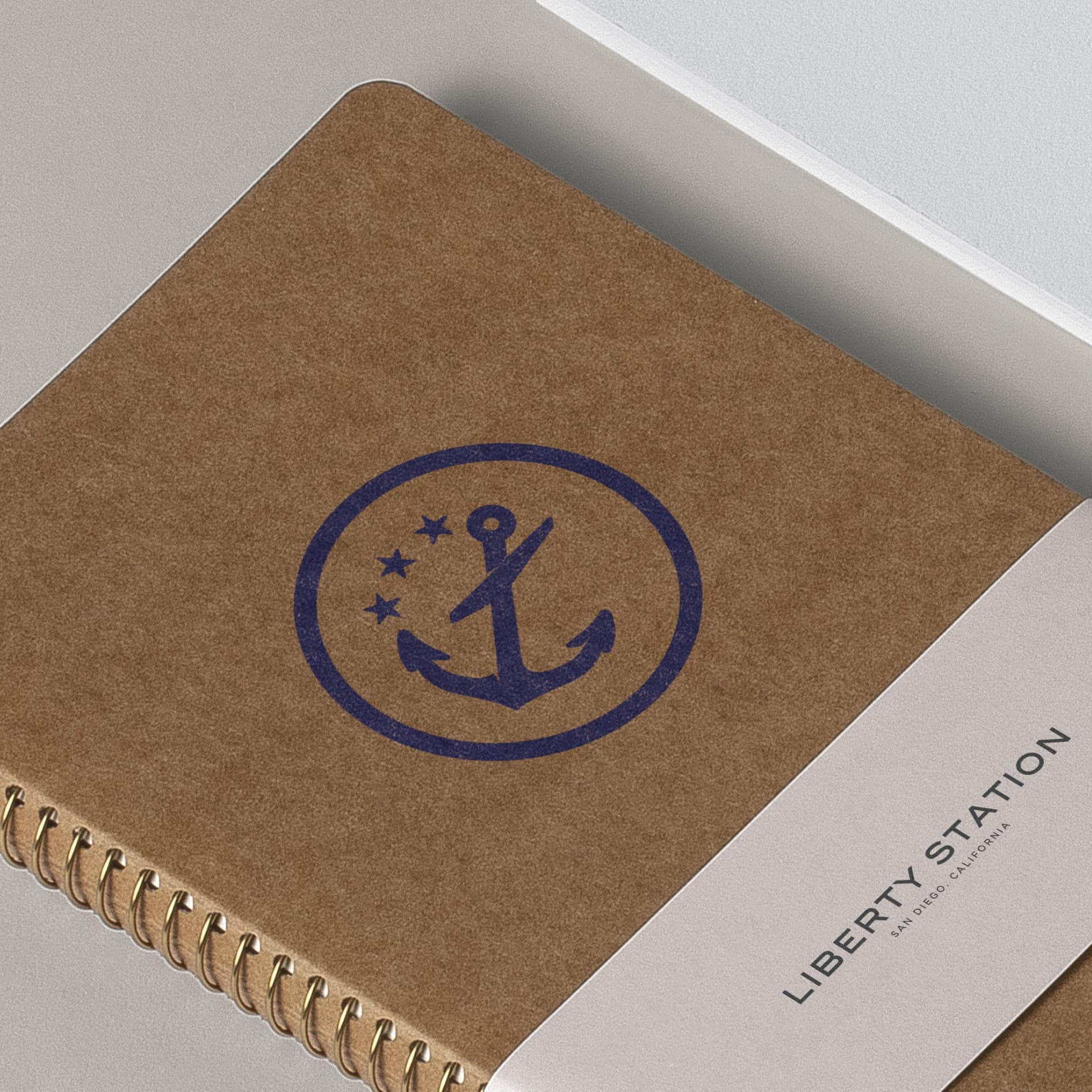 Logo with an anchor printed on a tan notebook stationary.