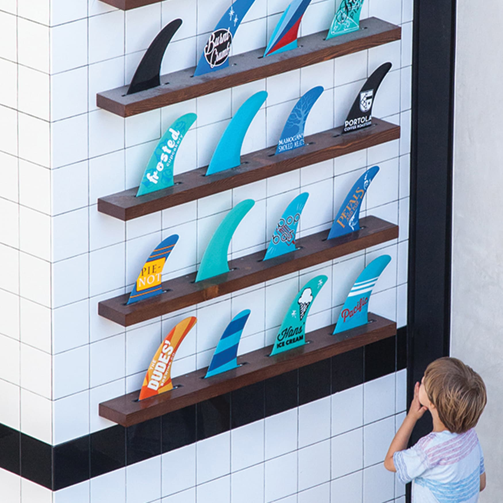 Pacific City specialty graphic installation of surf fins lined up on a wall covered in art and project information.